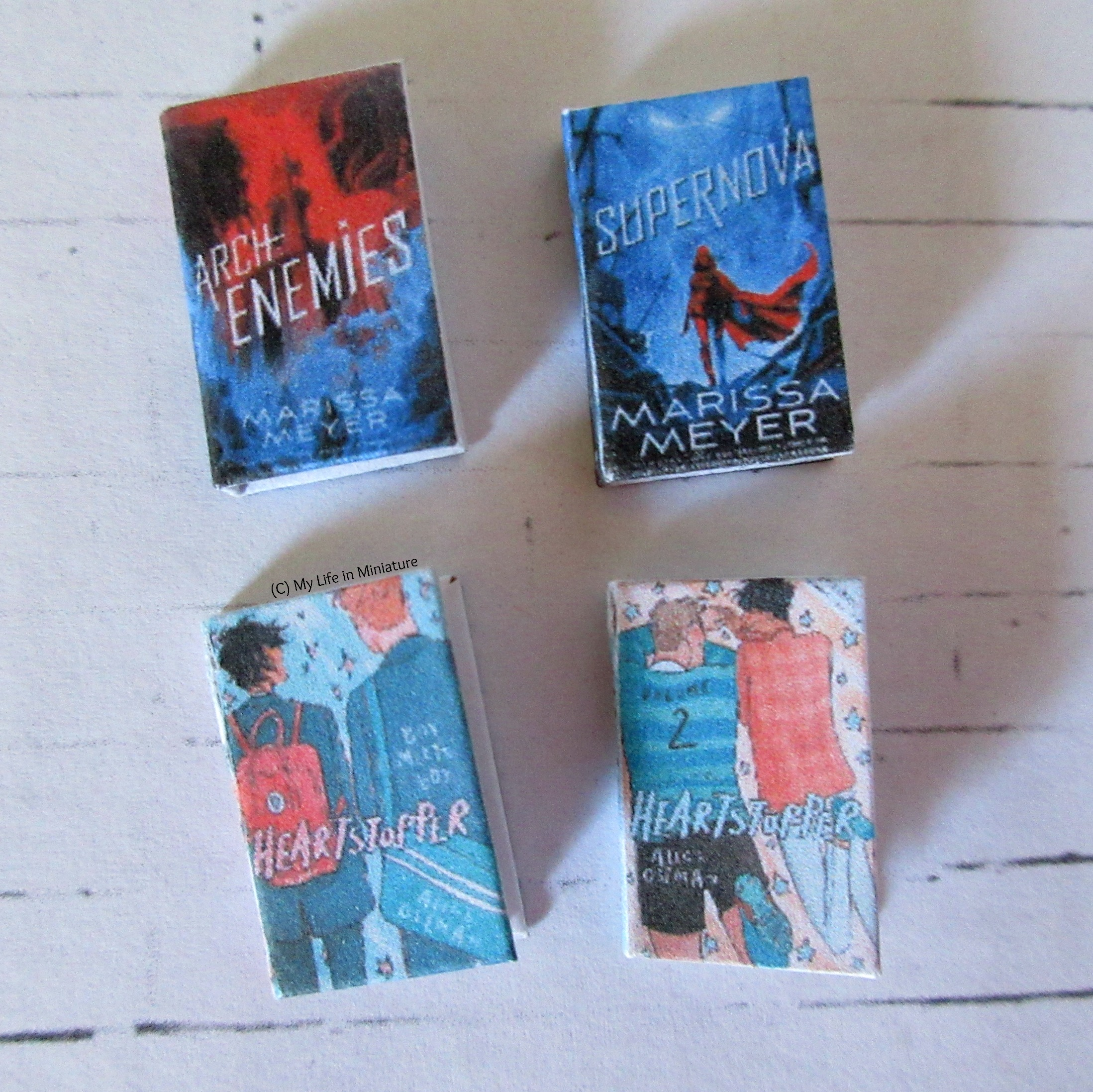 Four miniature books lie on a white brick background, covers facing the camera. Archenemies and Supernova by Marissa Meyer are above Heartstopper volumes 1 and 2 by Alice Oseman.