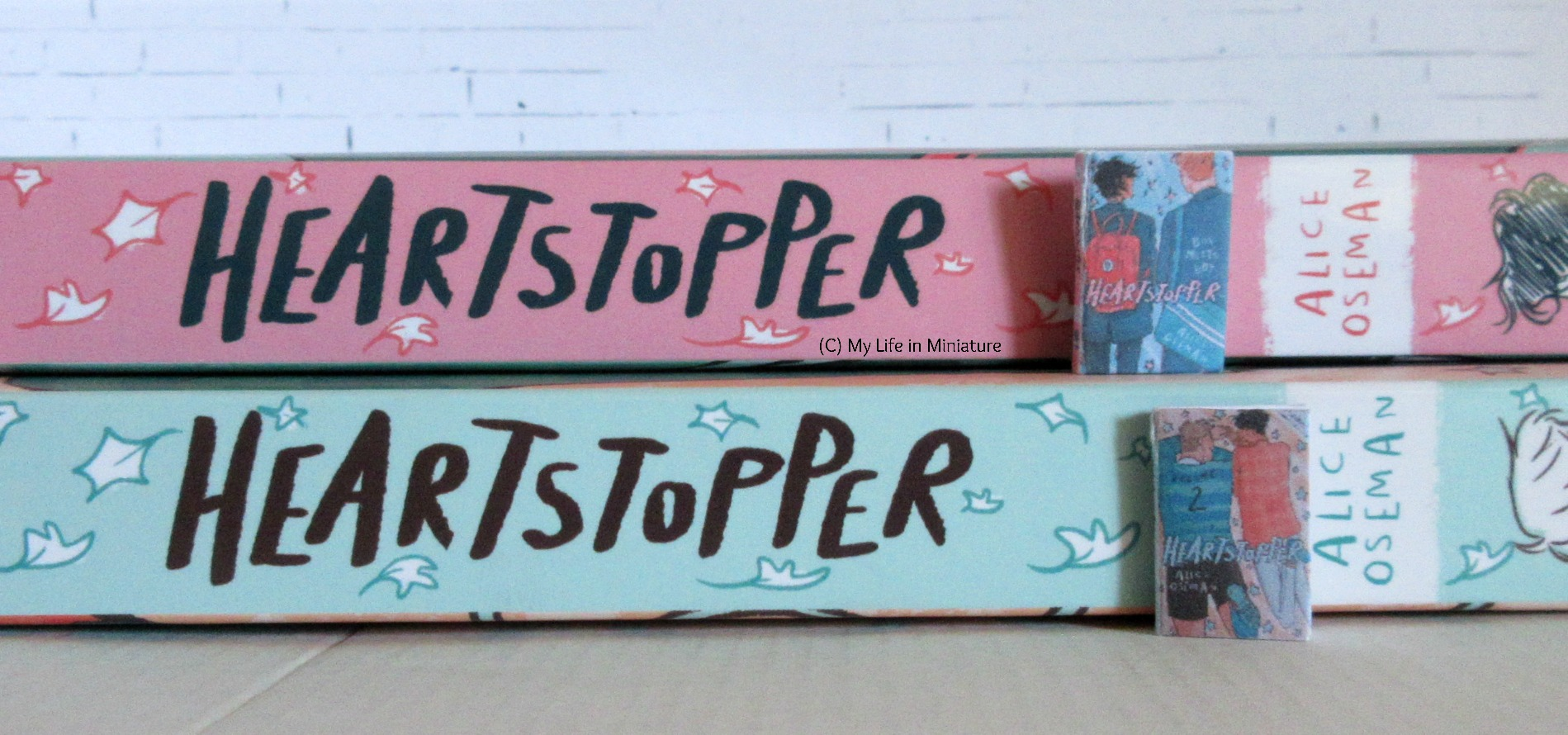 The two life-size Heartstopper volumes are stacked, spines facing the camera. The corresponding miniature version sits next to their matching life-size spines.