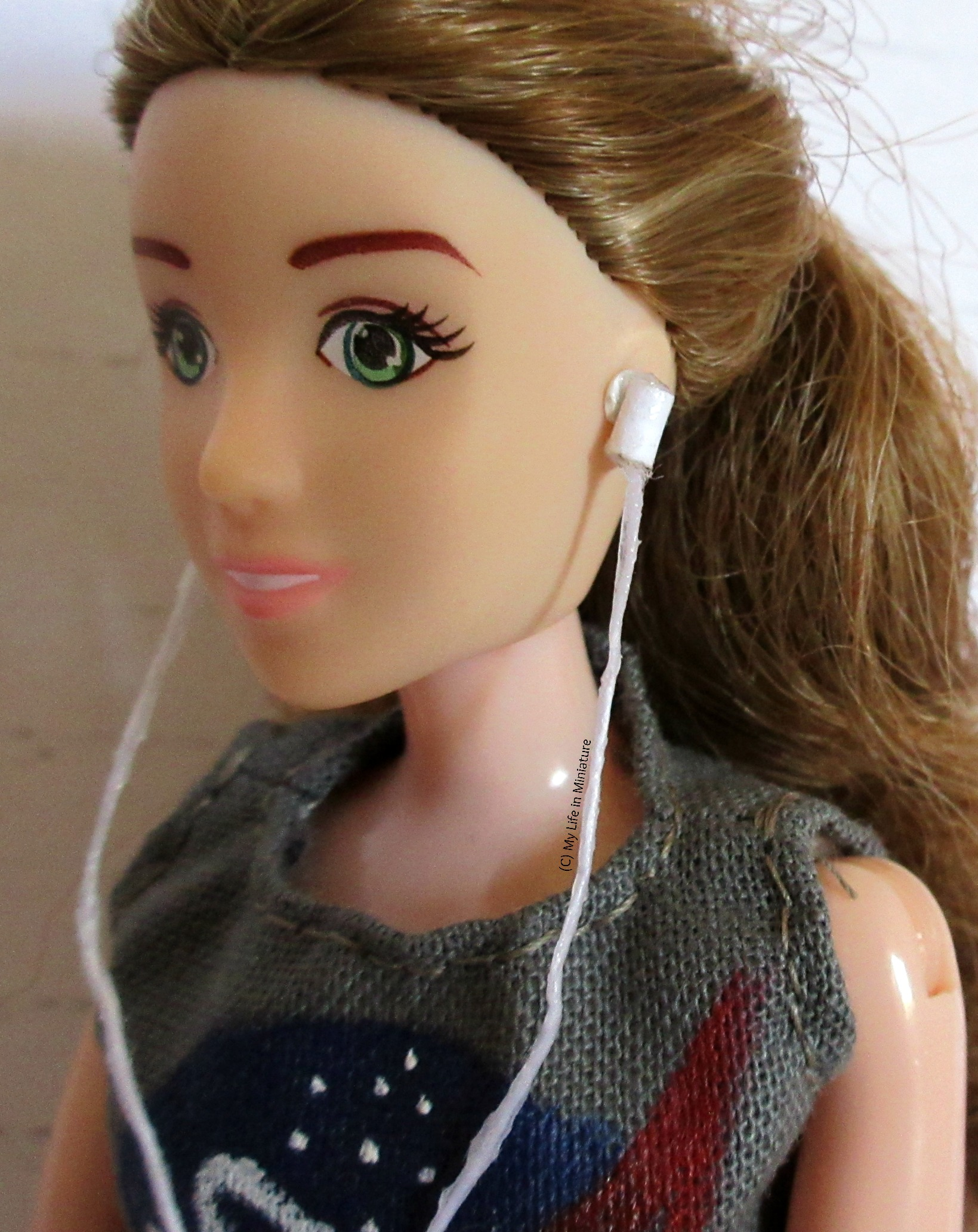 A close-up shot of one of the earbuds, as it sits blue-tacked onto Sarah's ear.