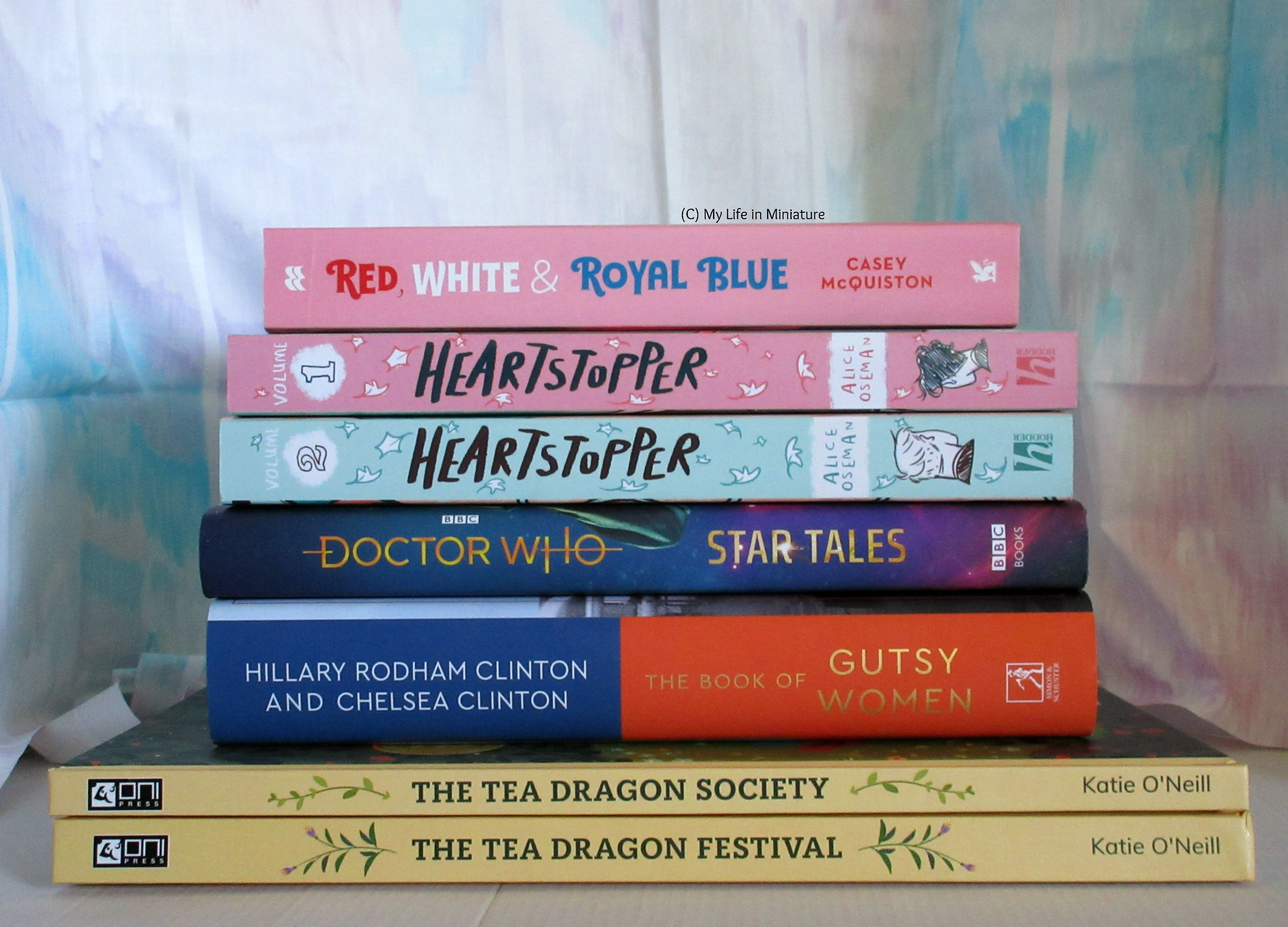 A stack of books, spines facing the camera. Top to bottom, the books are: Red, White and Royal Blue by Casey McQuiston, Heartstopper volumes 1 and 2 by Alice Oseman, Doctor Who Star Tales anthology, The Book of Gutsy Women by Hillary Rodham Clinton and Chelsea Clinton, The Tea Dragon Society and The Tea Dragon Festival by Kay O'Neill.