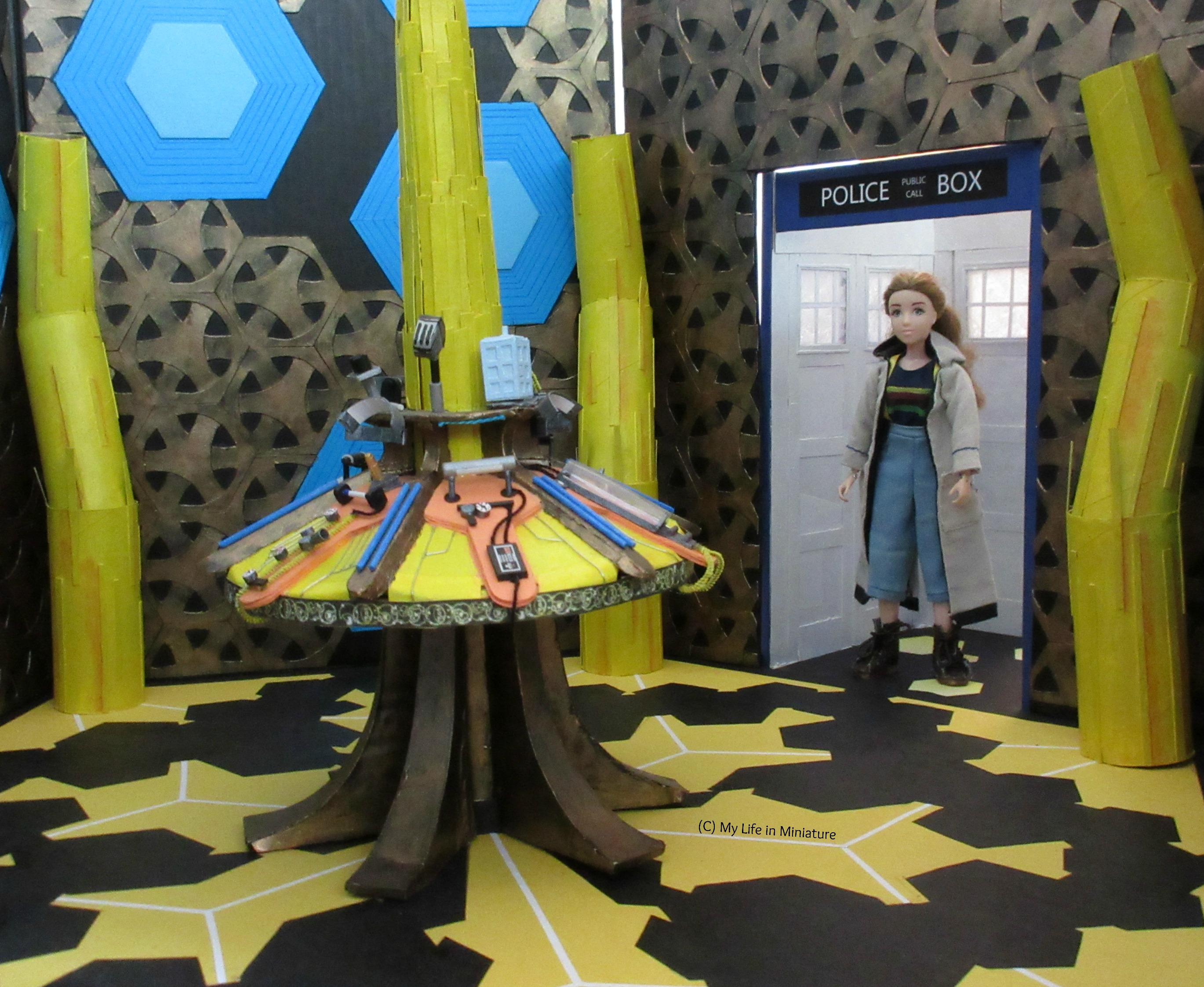 Sarah stands in the entryway of the TARDIS in Thirteenth Doctor cosplay, looking at the central console. Shot is taken at eye level.