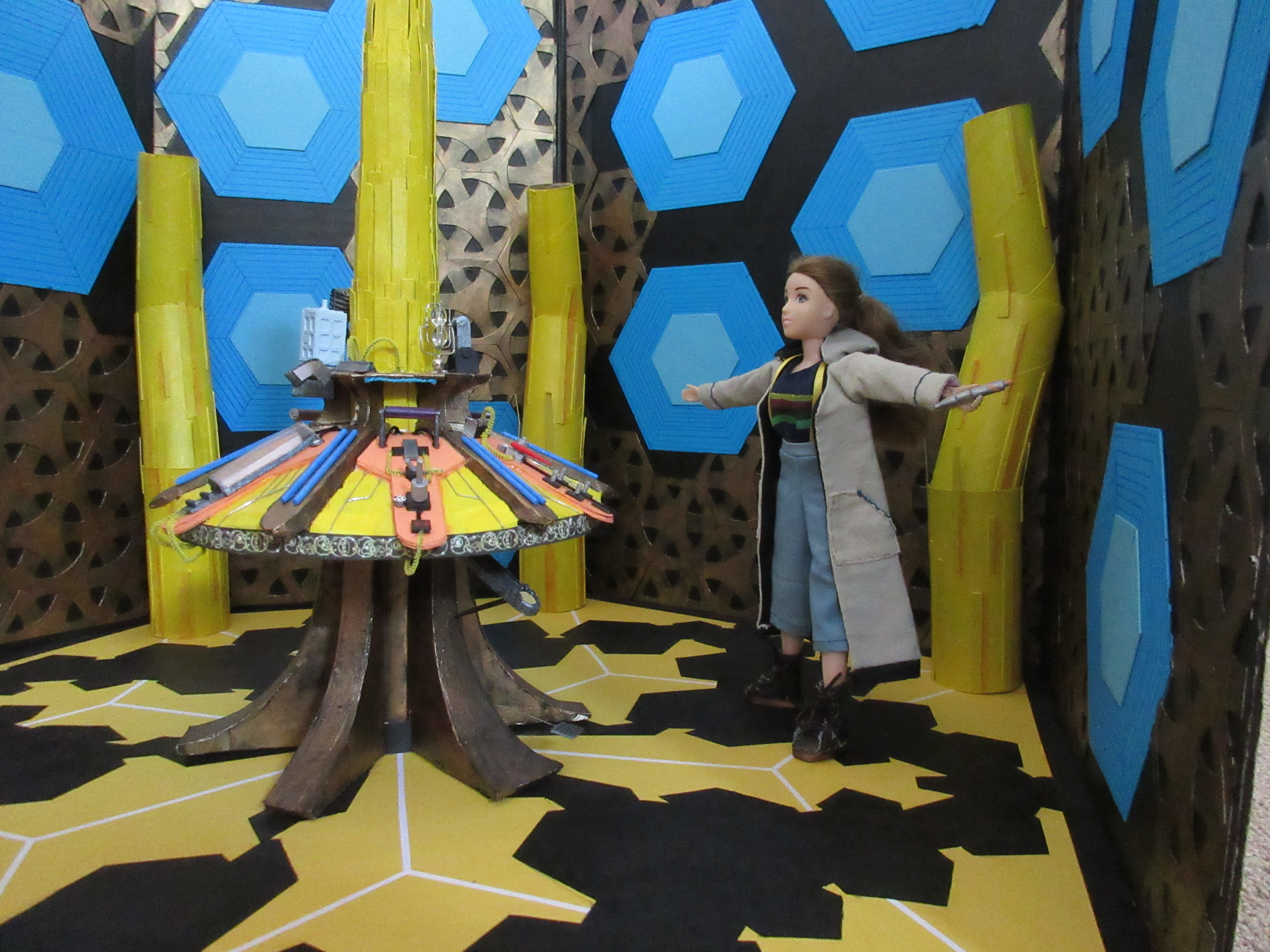 Sarah is in the TARDIS interior set in Thirteenth Doctor cosplay, holding the sonic screwdriver. She stands a distance away from the camera, arms flung wide. She is looking up at nothing in particular.