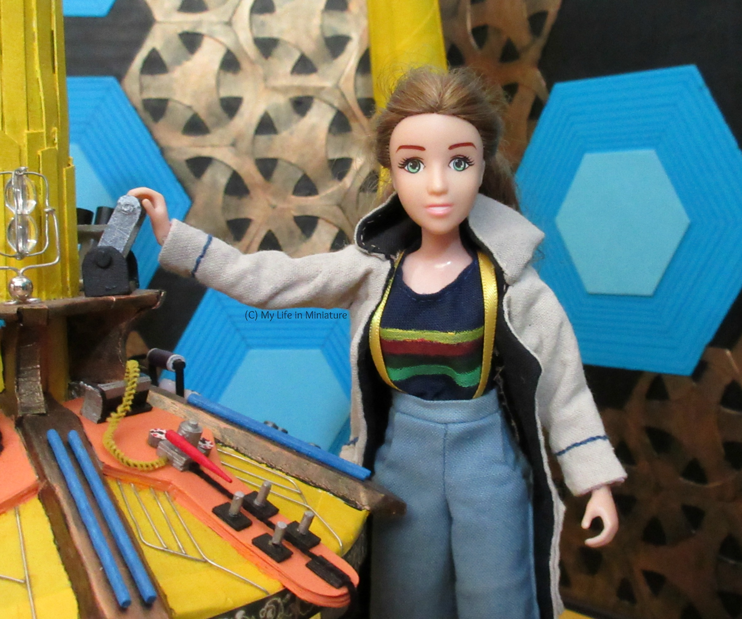 Relative close-up of Sarah at the central console in Thirteenth Doctor cosplay. Her hand is on the dematerialising lever, and she smiles eagerly at the camera.