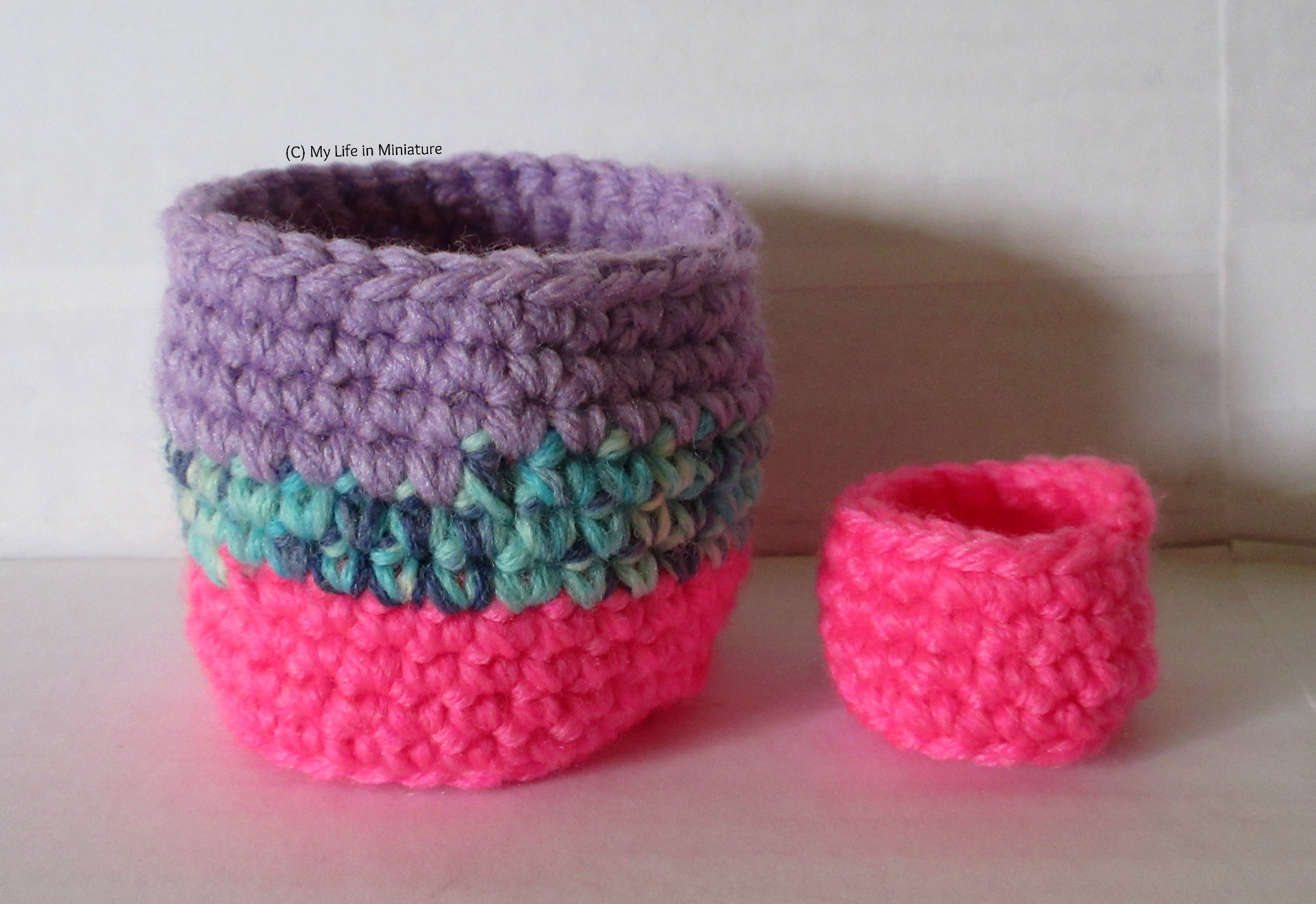Two crocheted birds' nest/cup-shaped objects stand side-by-side against a white background. One is larger and made of hot pink, variegated blue and plain purple yarn. The other is smaller and hot pink.