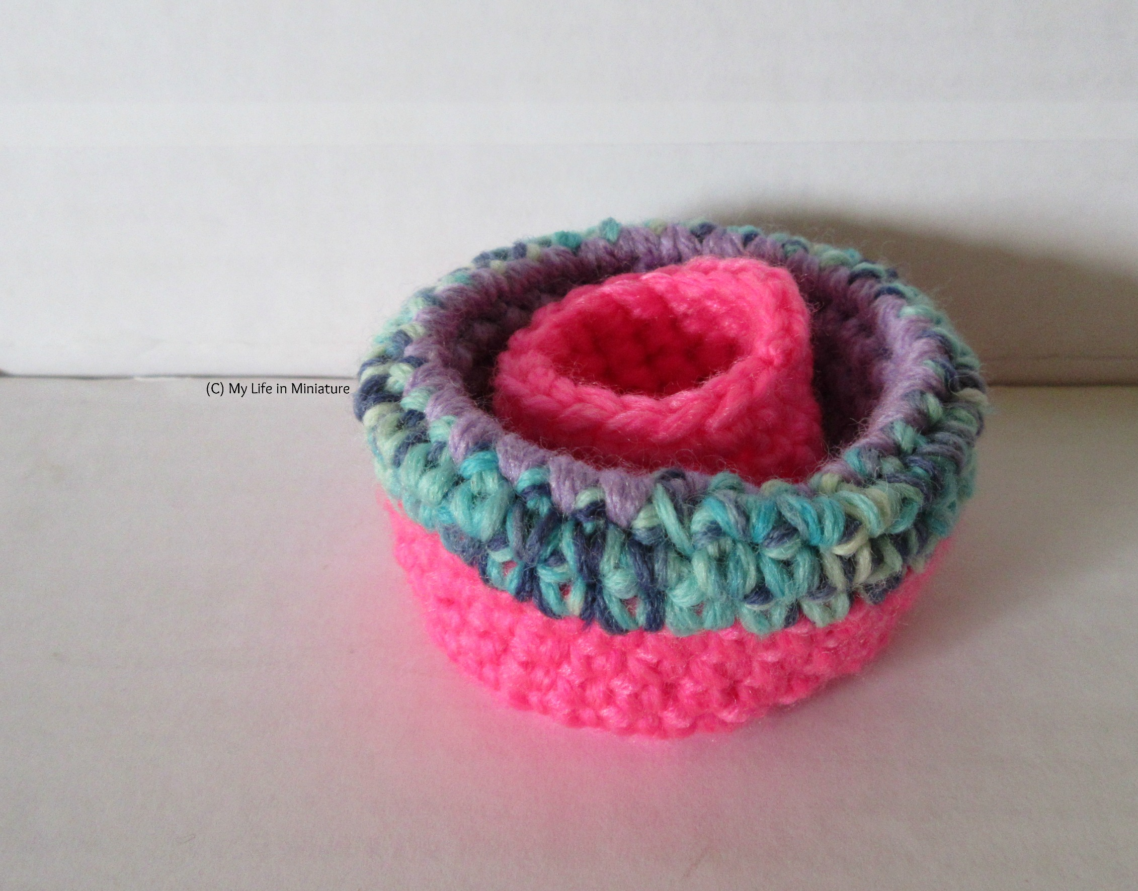 Image shows the larger birds' nest with its sides folded inwards, so the variegated blue yarn is visible. The small hot pink birds' nest is inside the larger one.