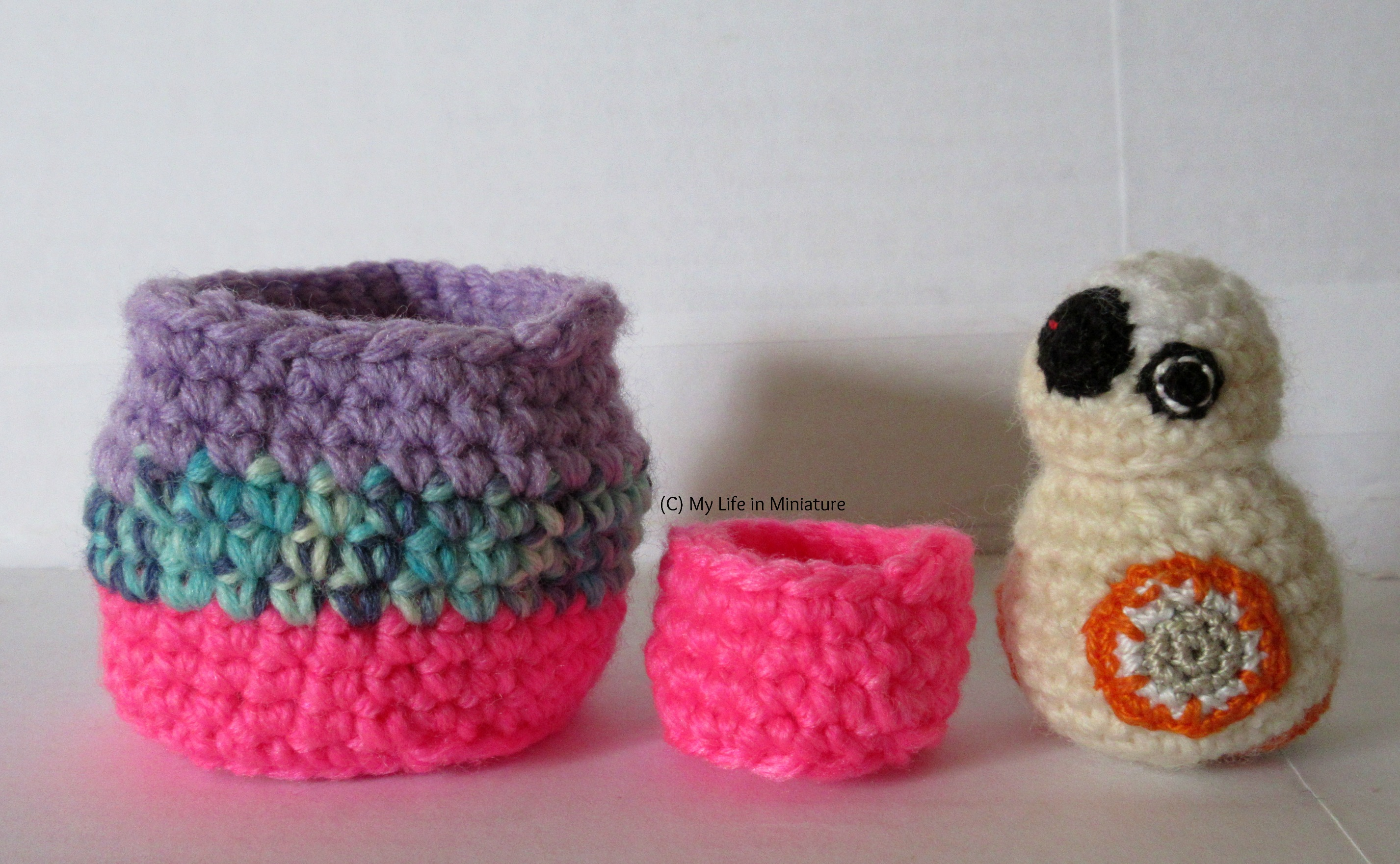 The two birds' nests sit beside a small crocheted BB-8, as a measure of their scale. The larger nest and BB-8 are about the same height, the smaller nest being about half the height.