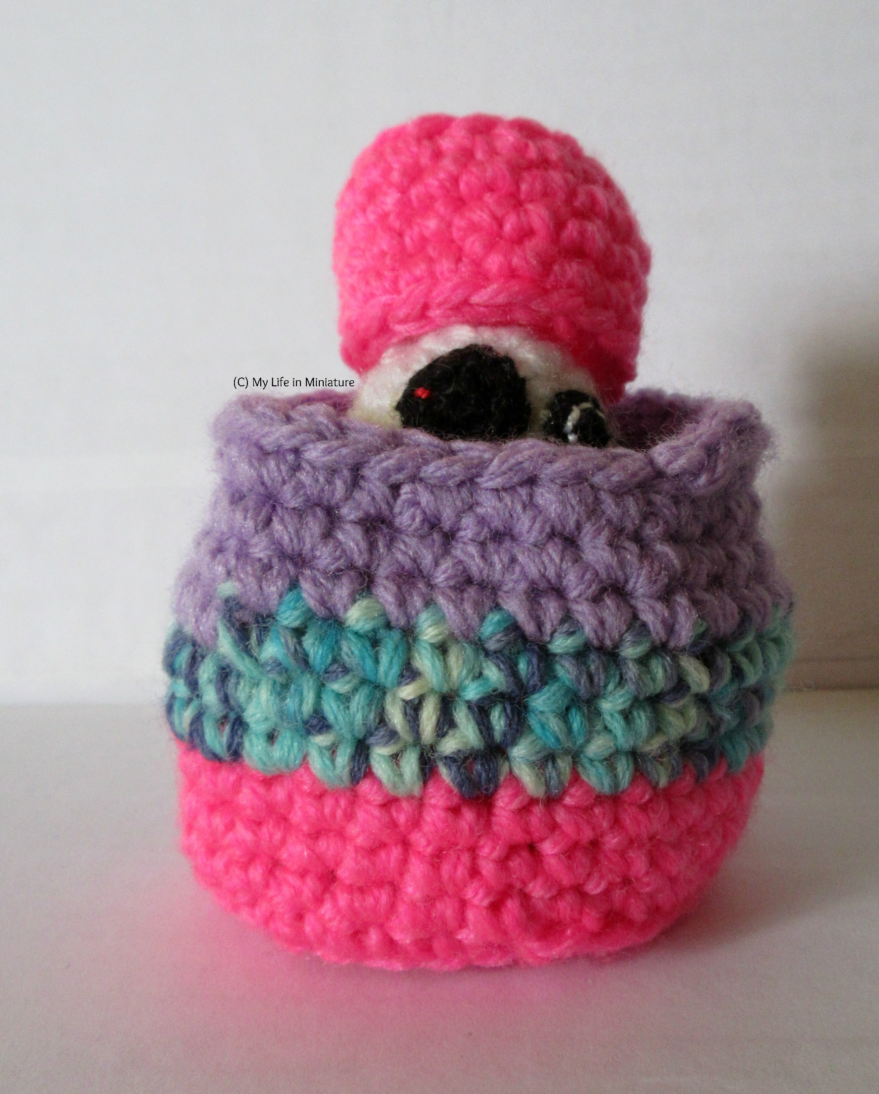 The crocheted BB-8 sits inside the larger nest, with the smaller nest perched on his head like a very large hot pink hat.