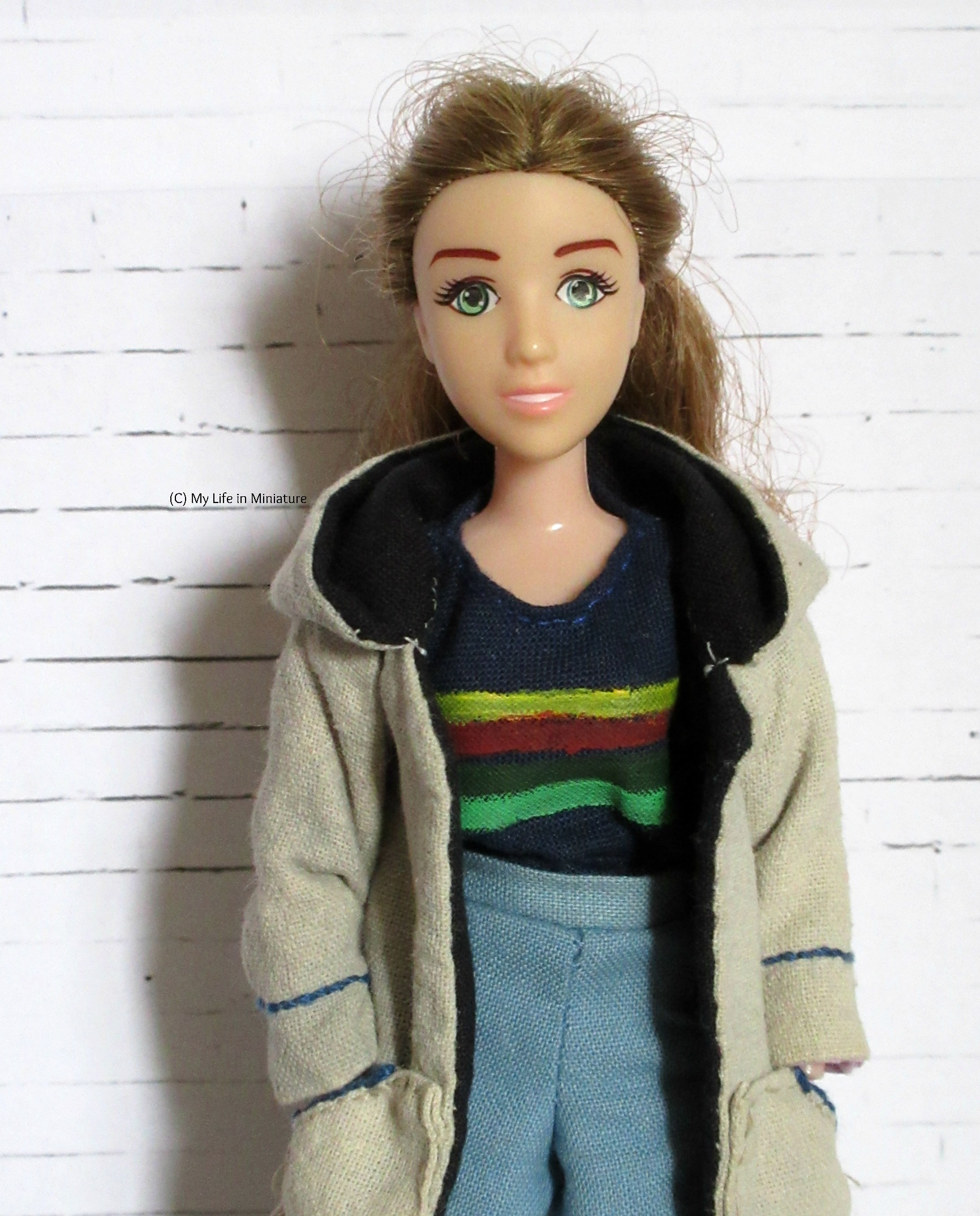 Sarah looks at the camera wearing Thirteenth Doctor cosplay. Her hands are in her pockets and she is against a white background.