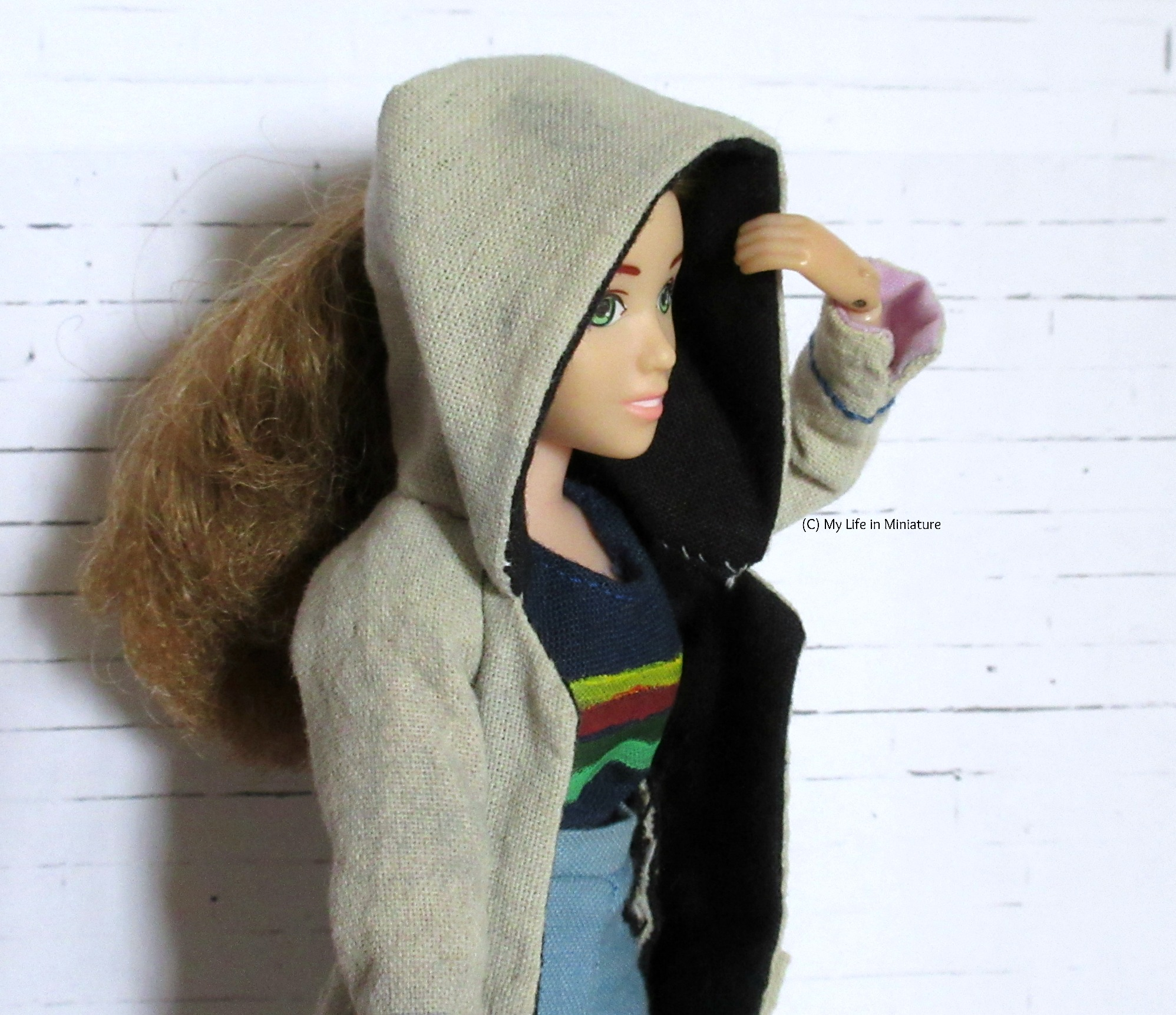 Sarah looks to the right of the image, and is against a white brick background. She wears Thirteenth Doctor cosplay, and has the hood of the coat up over her head. One hand is pulling it over, and her ponytail is visible behind the hood.