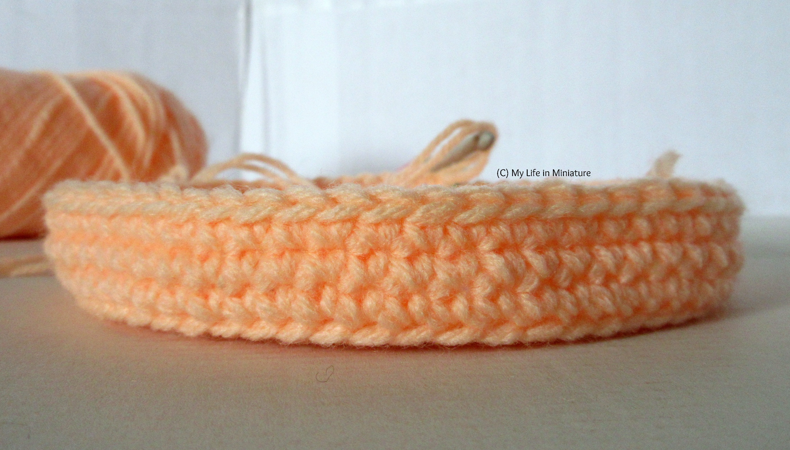 Side-on shot of the orange birds' nest; three rounds of the sides are complete. The hook and yarn are visible in the background.