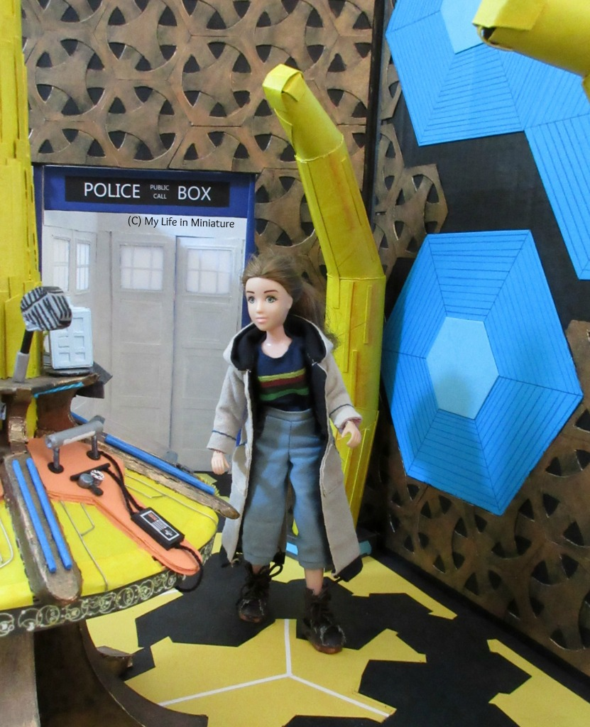 Sarah walks towards the camera inside the TARDIS interior set, wearing Thirteenth Doctor cosplay. She is looking at the central console (which is in the foreground), and a complete yellow pillar and the entrance are in the background.