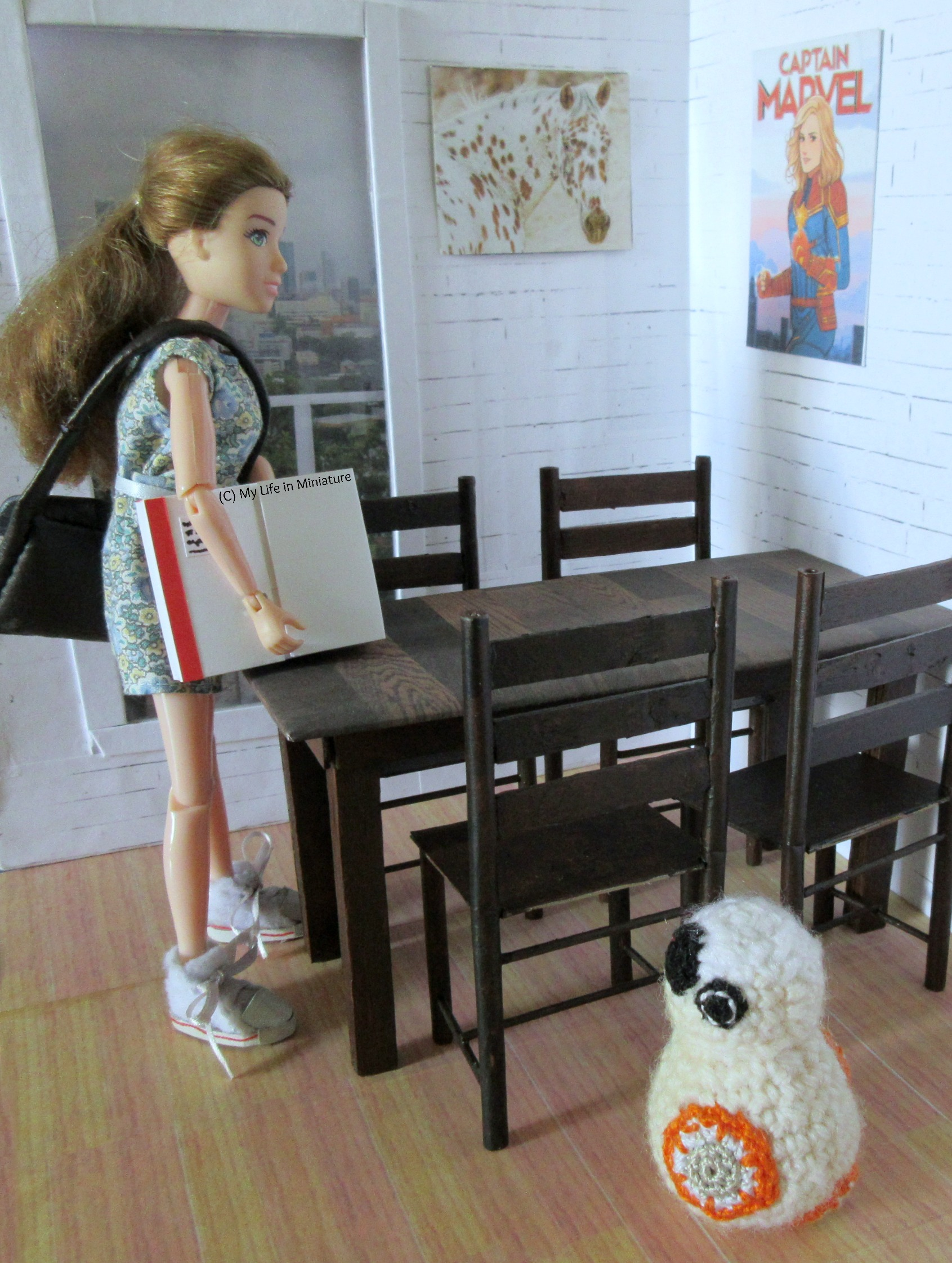 Sarah is placing a large parcel box on her dining room table while BB-8 watches on. She has her brown satchel with her, having just got home.
