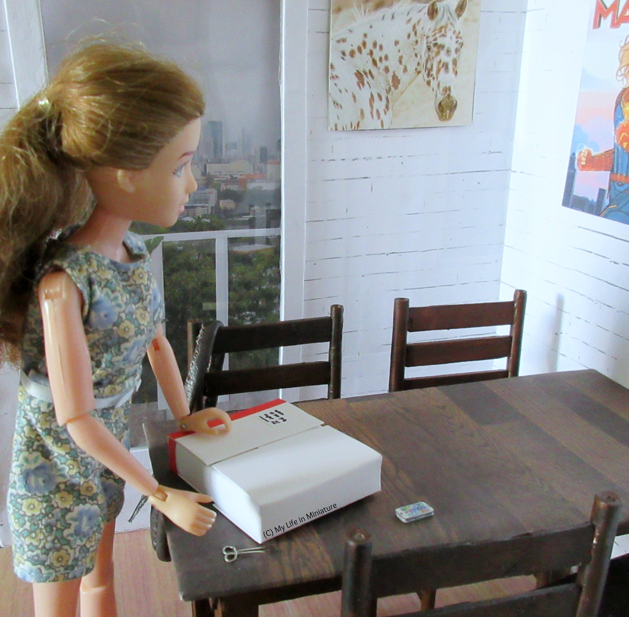 Sarah is looking down at the parcel on her table, trying to remember something. Scissors and her mobile phone are also on the table, and her bag is over the back of a chair.