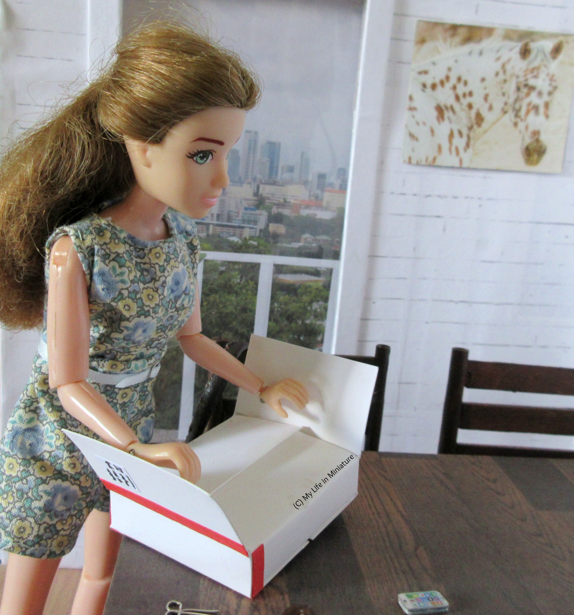 Sarah looks down at the parcel on her table as she opens the top two flaps. The flaps underneath prevent the box's contents from being seen.