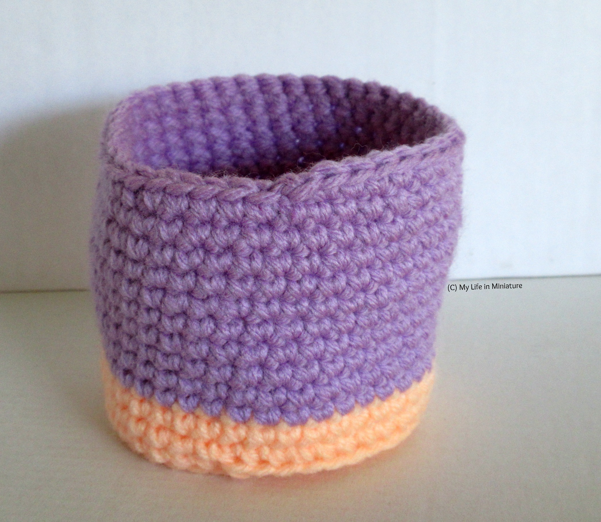A crocheted nest sits against a white background. The base and first two rounds of the sides are orange, and the rest of the sides are purple.