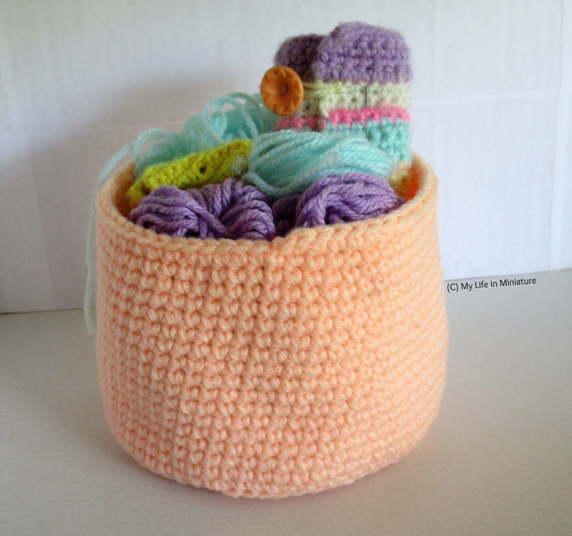 An orange nest sits against a white background, filled with yarn, a crocheted hook roll, and a small yellow pouch holding stitch markers.