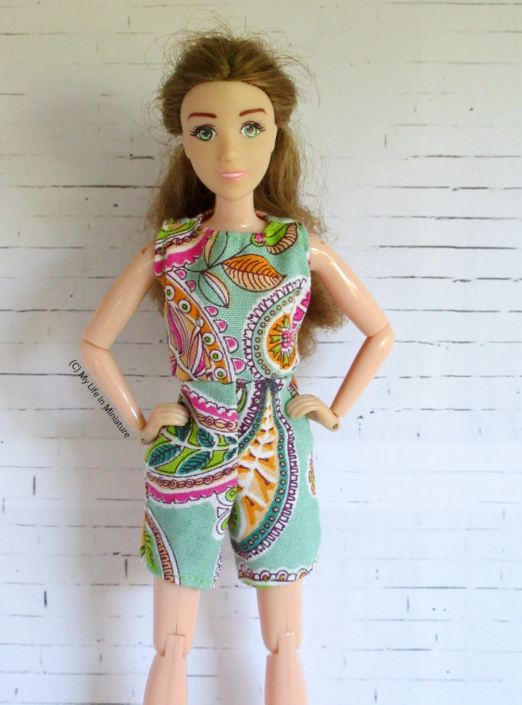 Sarah wears her new playsuit against a white brick background, hands on hips. The fabric is pale green with pink, green and orange paisleys on.