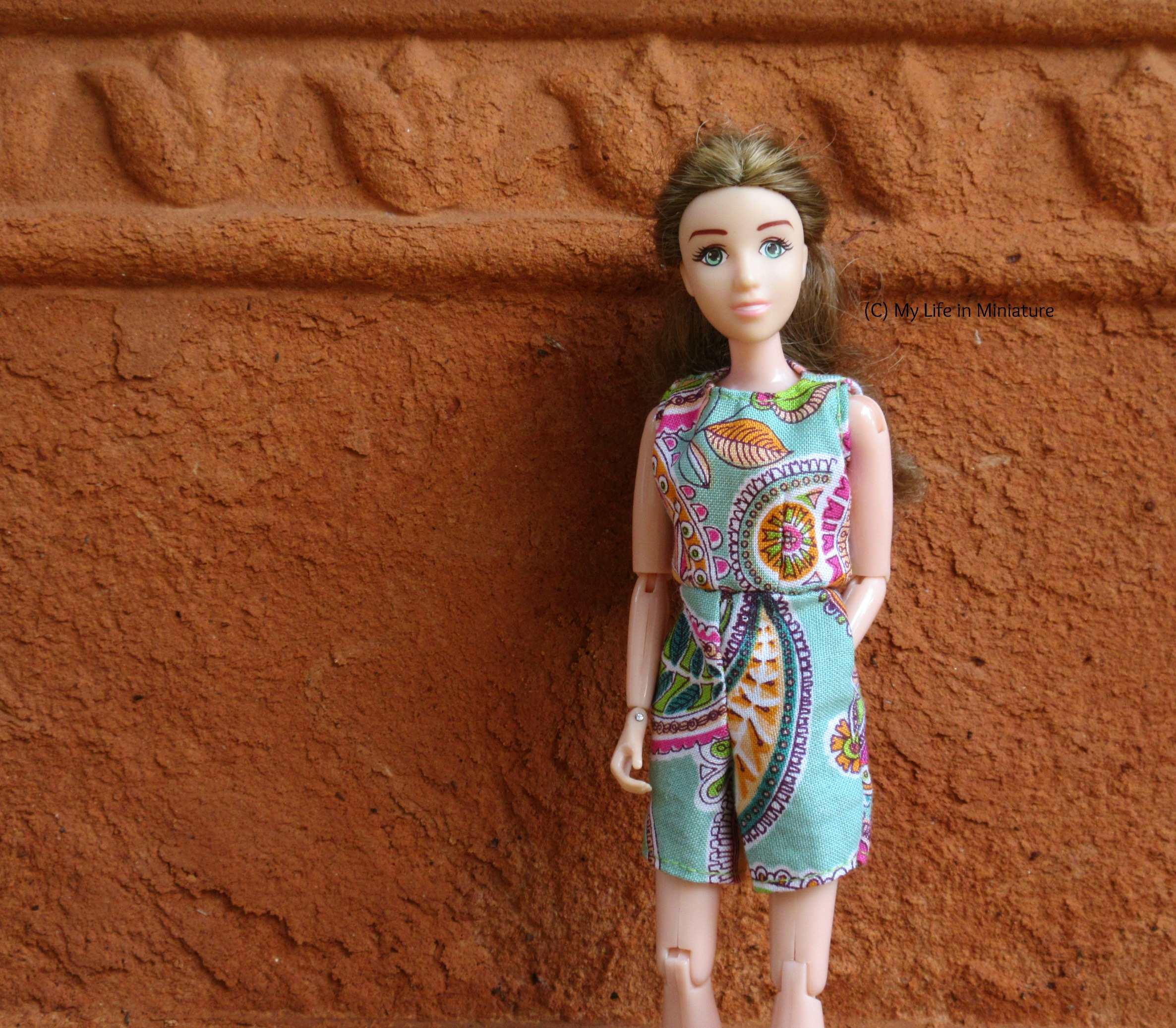 Sarah wears the playsuit with one hand in her pocket and the other hanging beside her. She looks at the camera, and is standing against a rough terracotta background.
