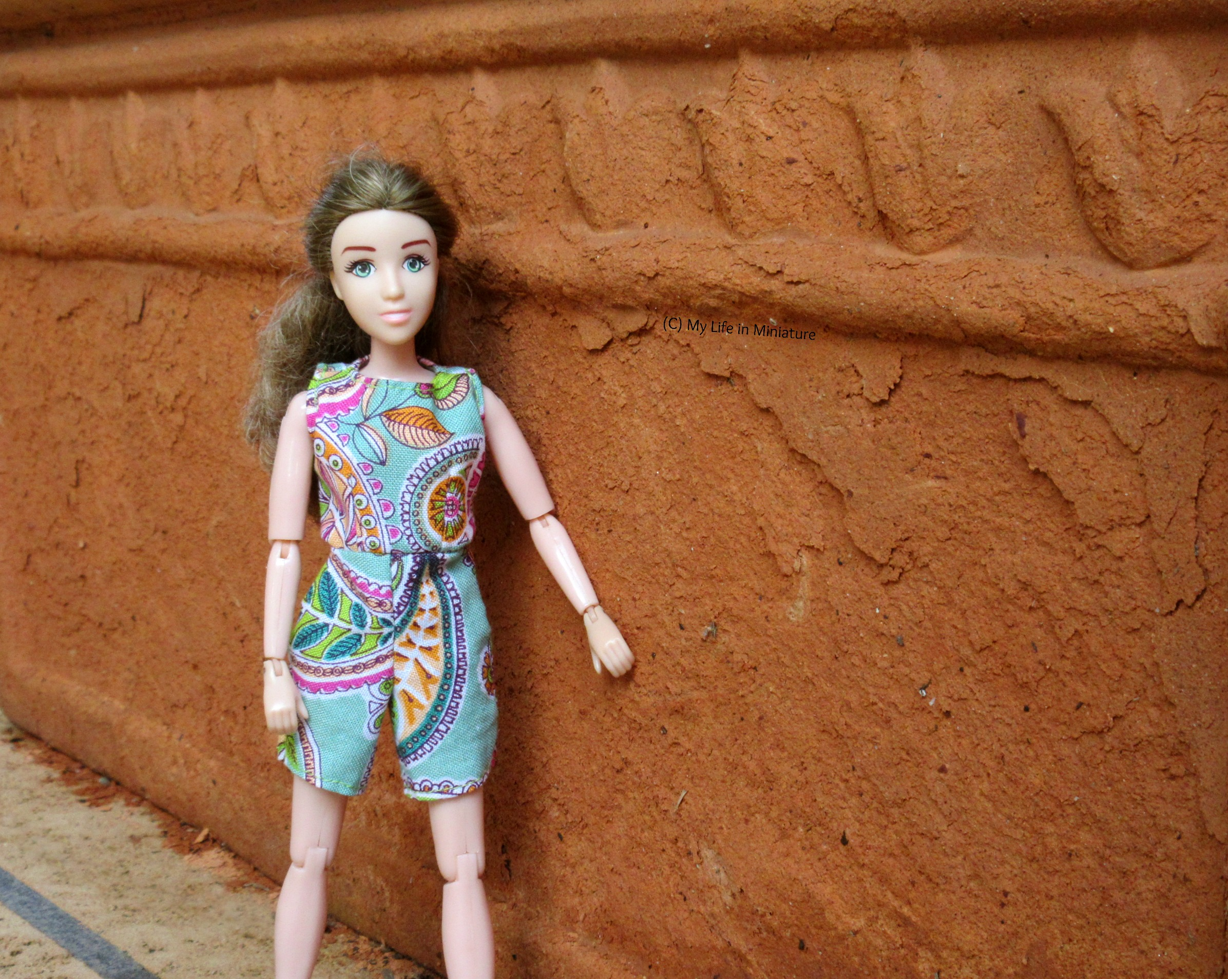 Sarah walks beside a terracotta pot, one hand trailing along the rough surface. She looks at the camera.