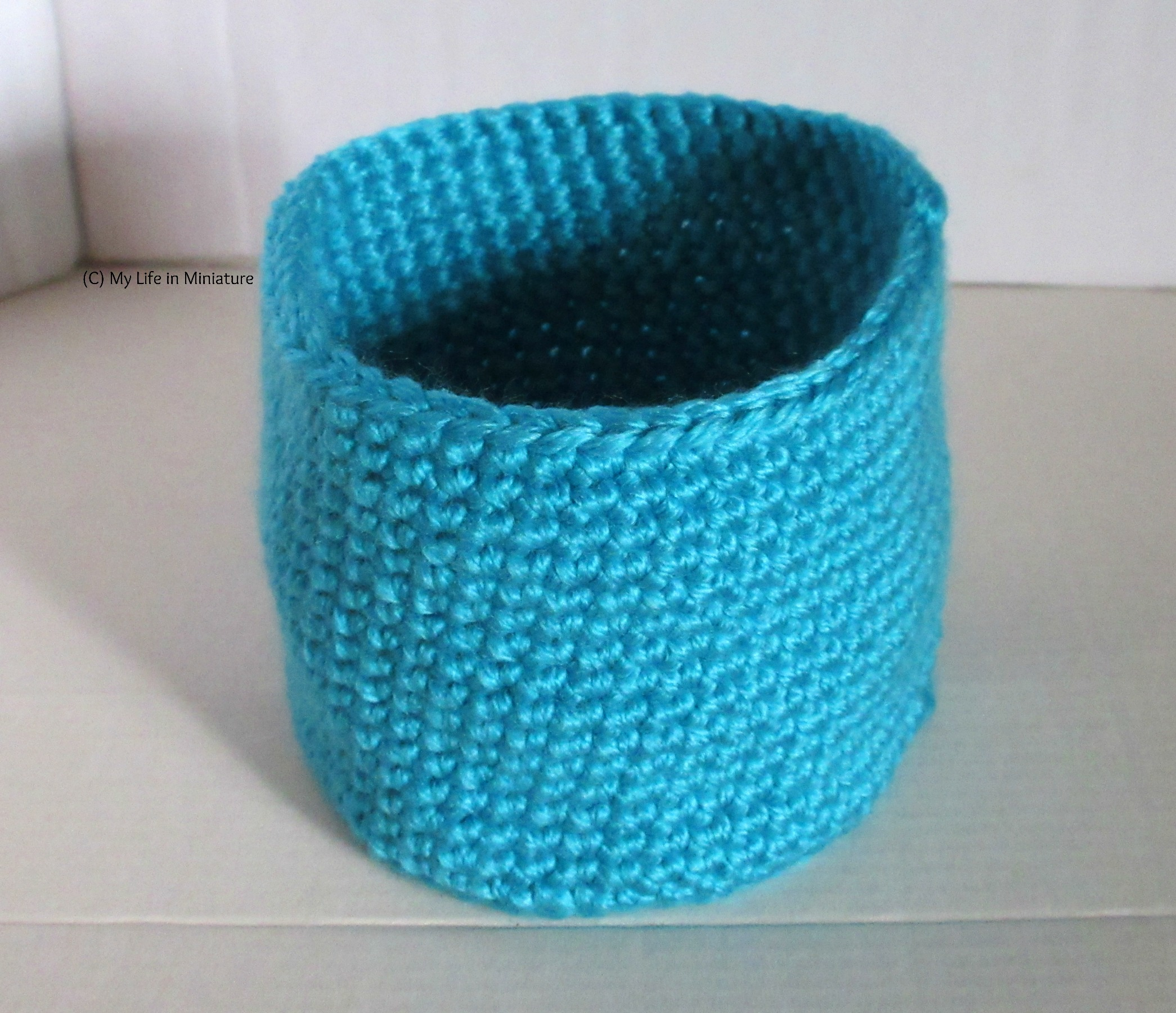 A blue crocheted nest sits against a white background.