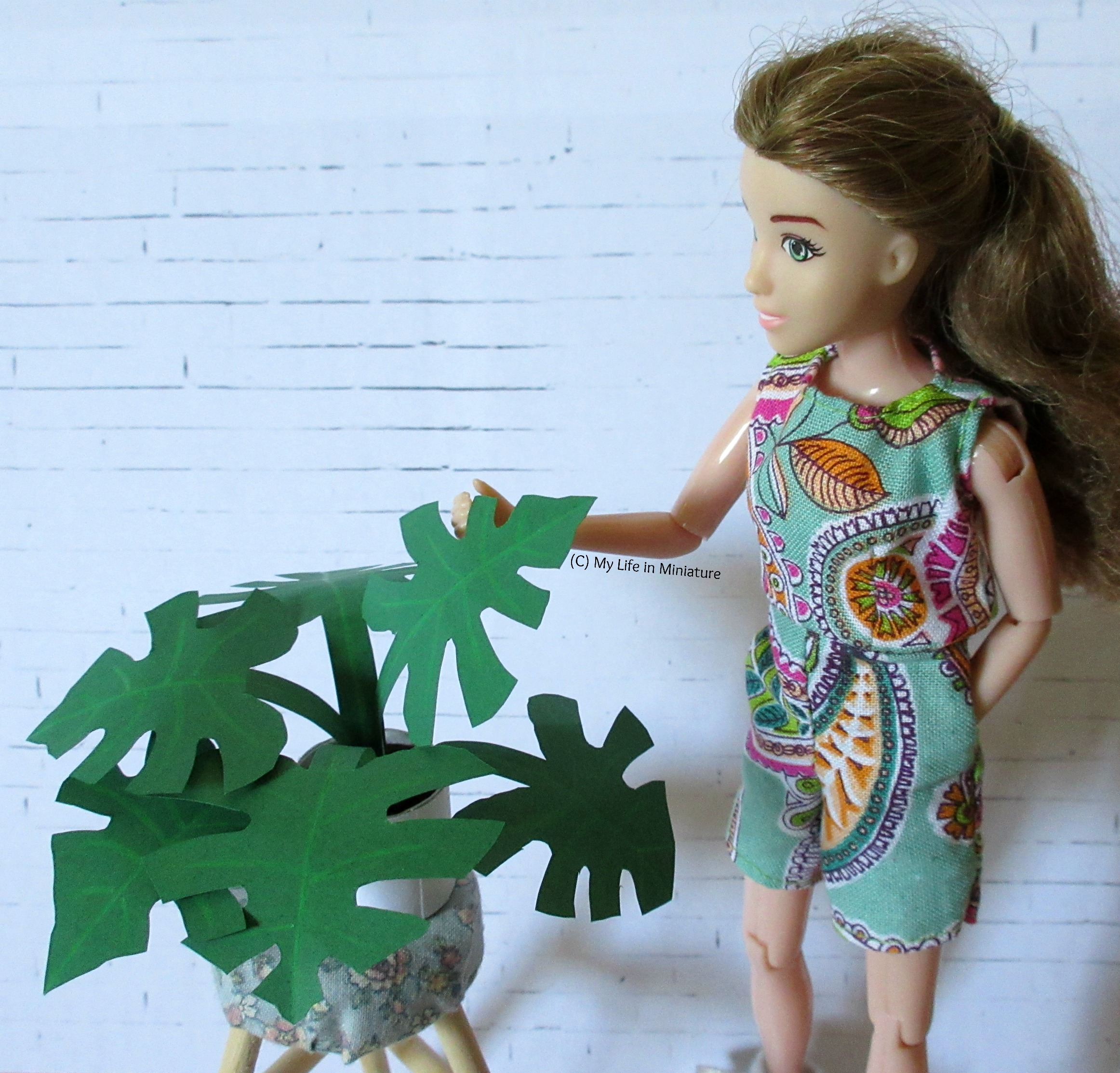 The monstera plant sits on a stool next to Sarah. who is examining one of its leaves.