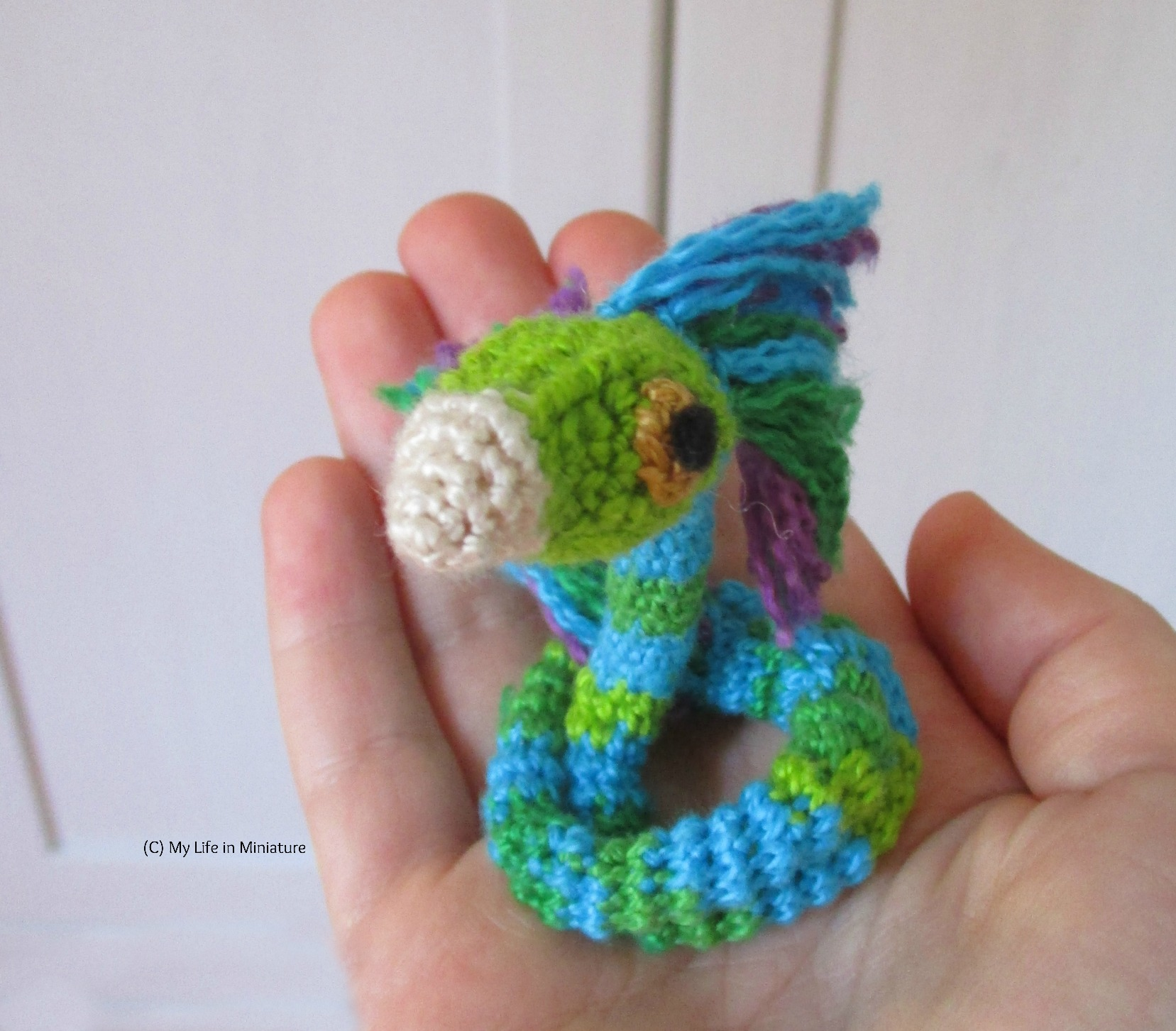 A crocheted Occamy sits coiled in the author's palm. Its beak and face are tilted up towards the camera.