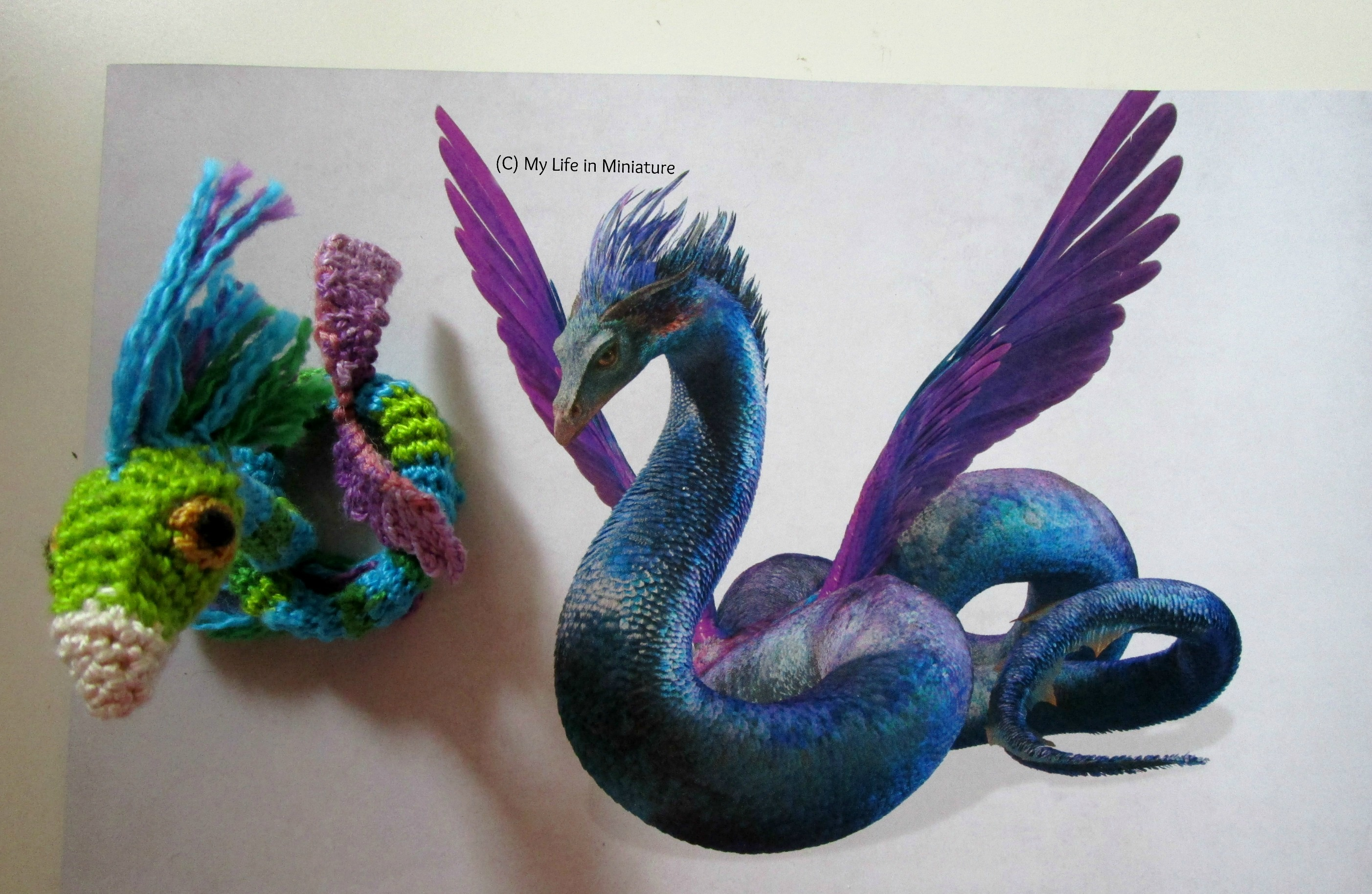 Aerial shot of a crocheted occamy sitting coiled on a book page. The occamy looks up at the camera, and the book page has an image of a concept art occamy.