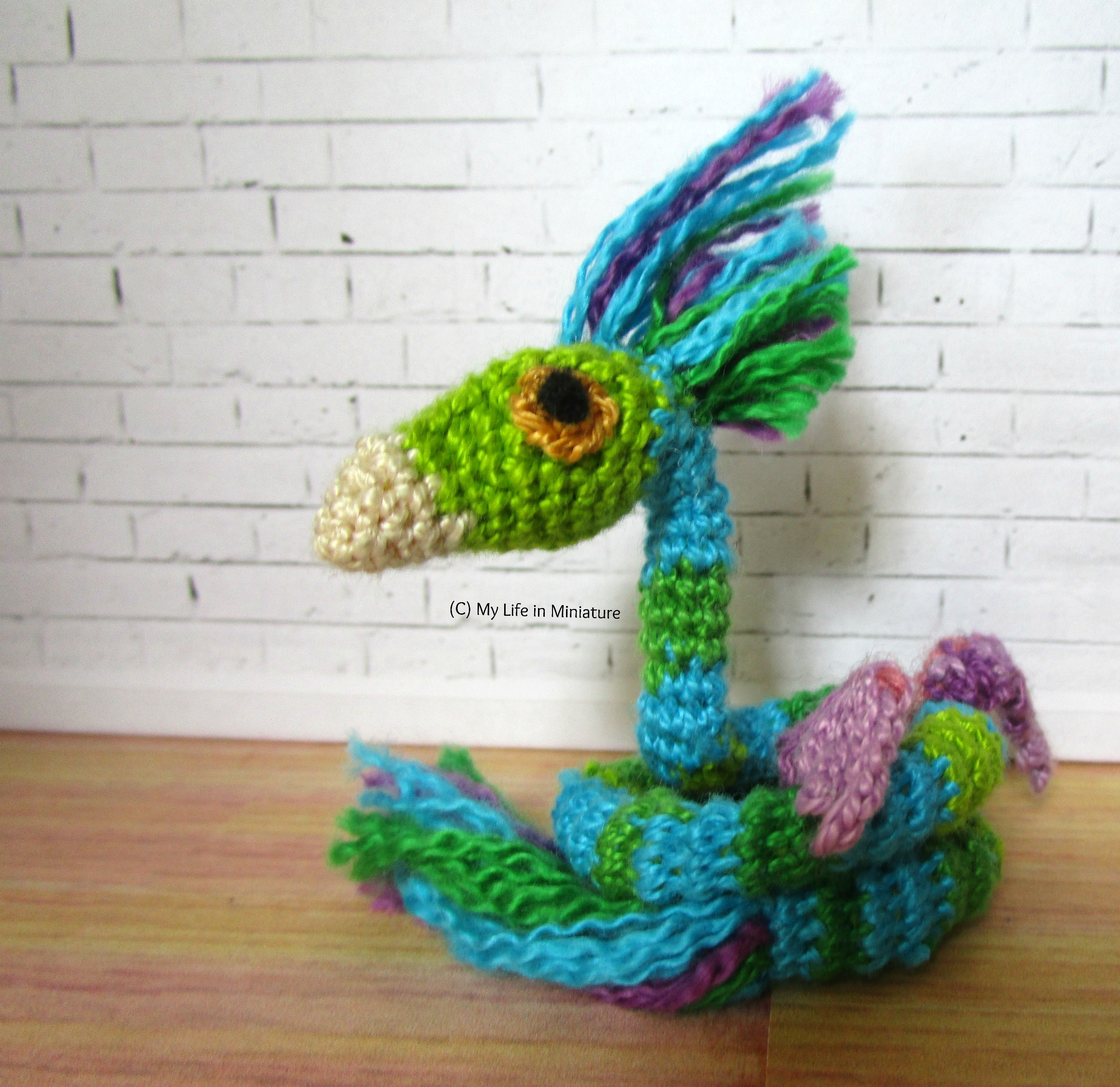 A crocheted occamy sits coiled up against a white brick background. It's a fantasy creature, a lot like a snake with wings and a birds' head. This one is various shades of blue and green with pale purple wings.