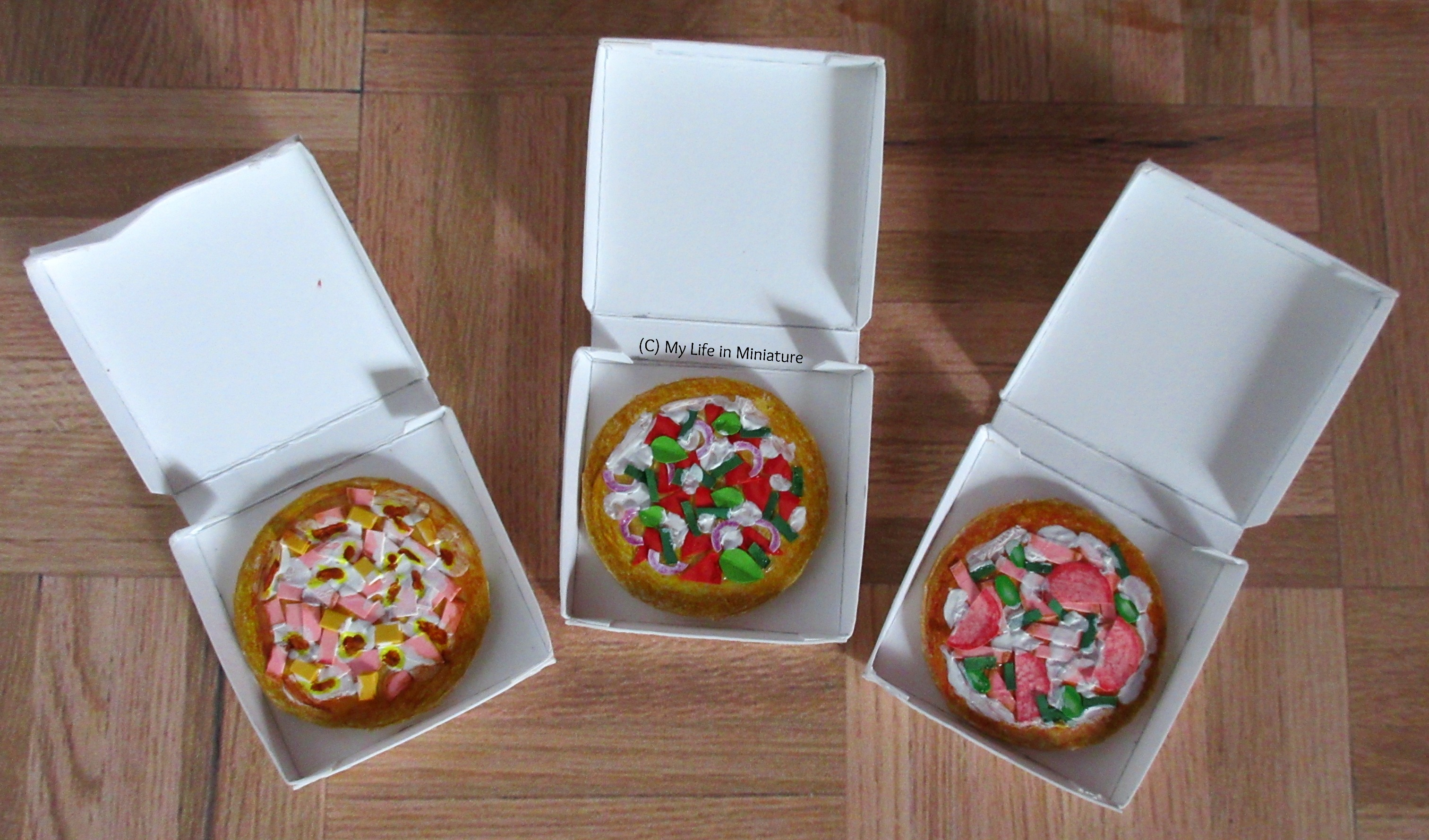 The three pizza boxes sit open on a wood parquet background. On the left is a ham and pineapple, the centre vegetarian, and the right a supreme pizza.