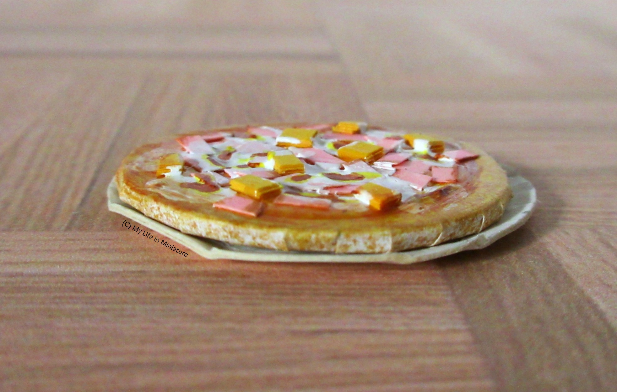 Close-up shot of the ham & pineapple pizza from the side, so the 3-D-ness of the toppings are visible. The pizza is on a plate, and sits on a wood parquet background.