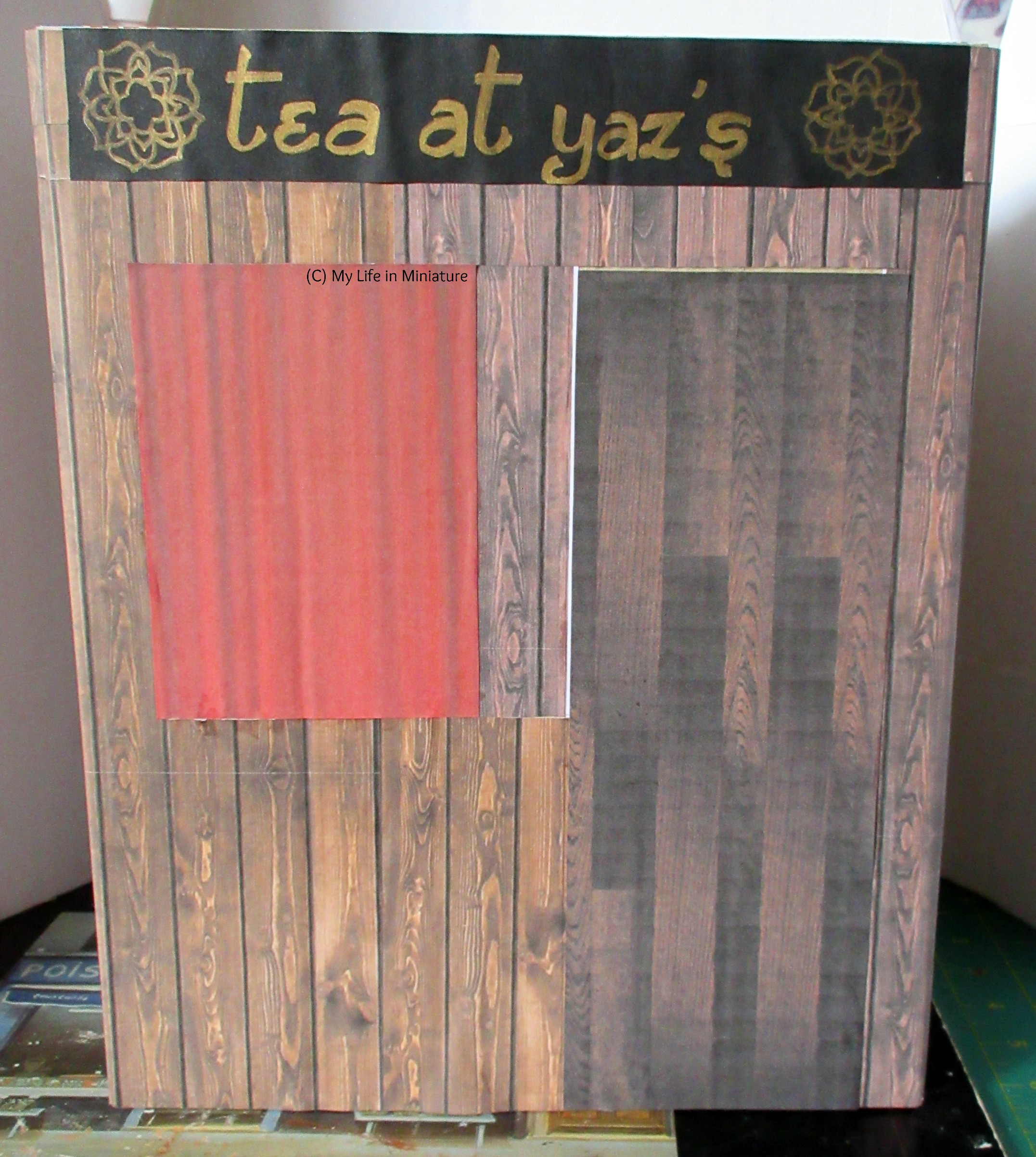 A cereal box sits on a protective mat, covered in dark wood-printed paper. Across the top is a black strip with 'Tea at Yaz's' written on it in gold. Underneath it to the left is a rectangle of red paper.