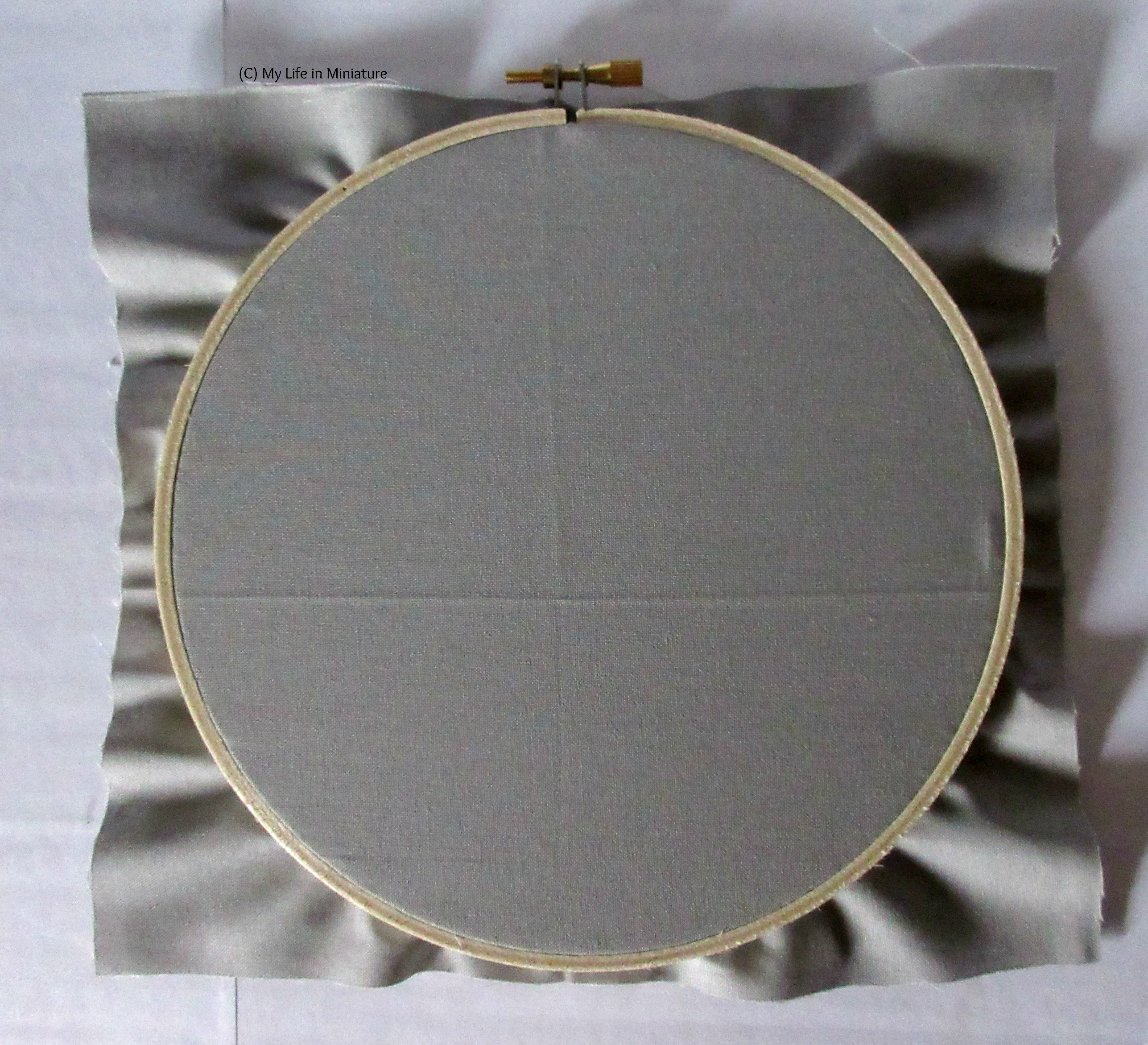 An embroidery hoop sits on a white background, filled with grey cotton.