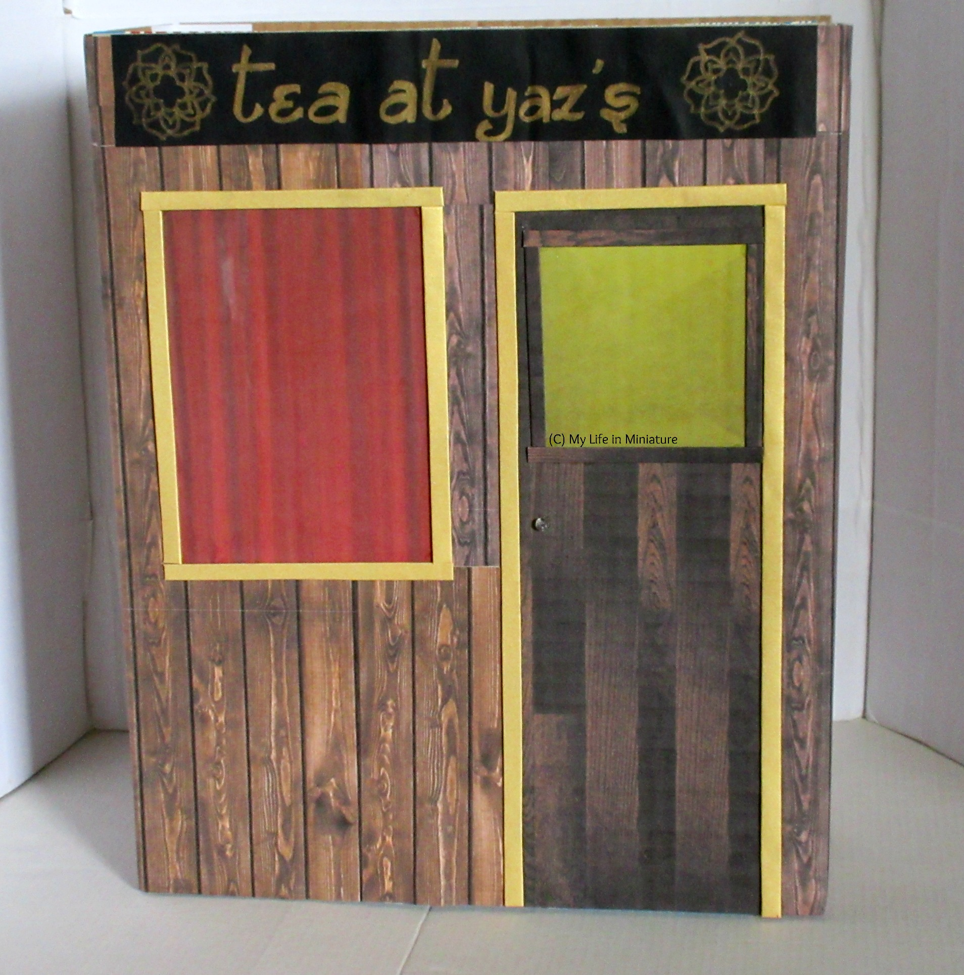 The wood-covered cereal box looks more like a shopfront now. The red rectangle is surrounded by gold trim, and next to it is a door. The door is also dark wood with a yellow window in the top, and is also surrounded by gold trim.