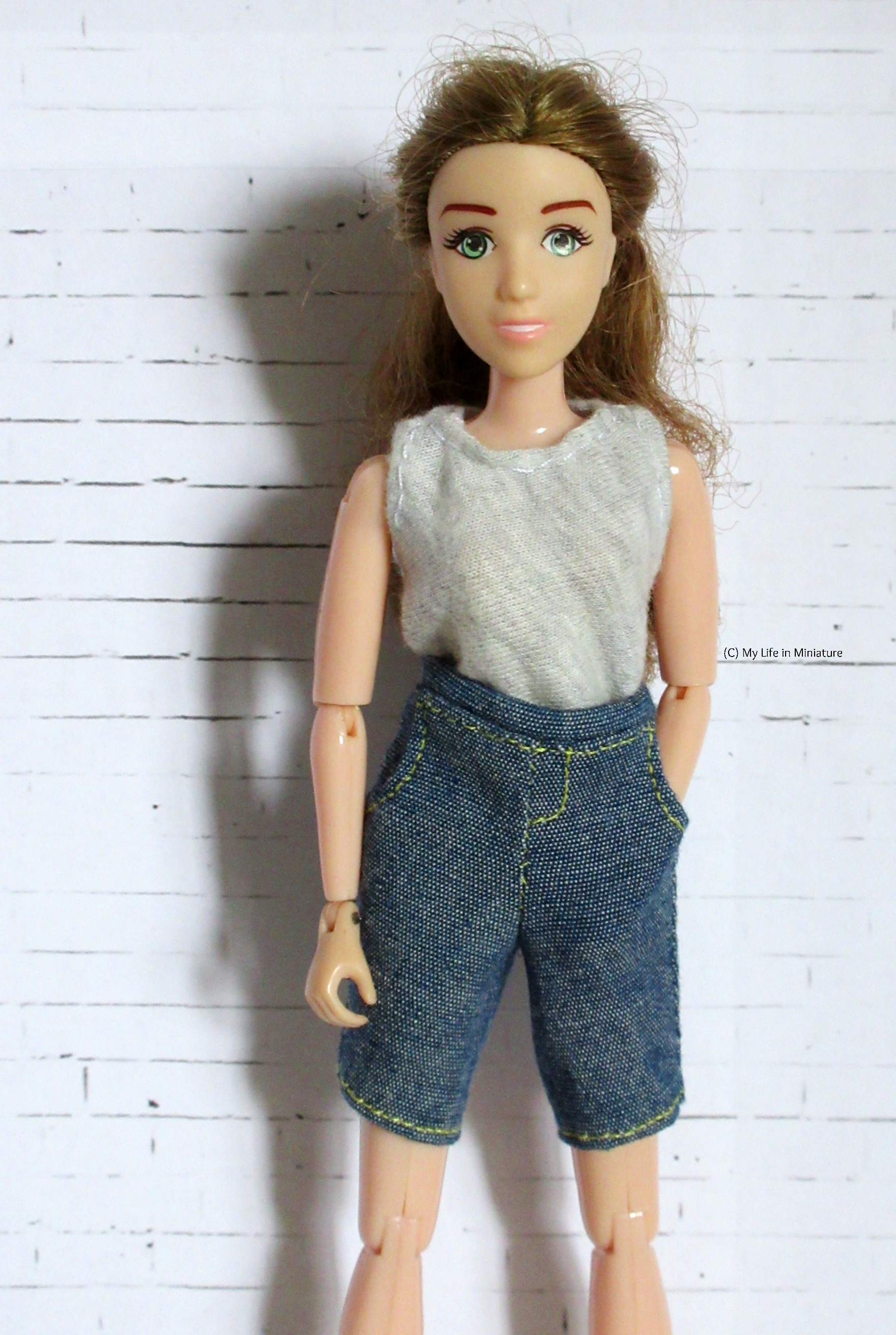 Sarah stands in front of a white brick background, looking at the camera. She wears a grey shirt tucked into a pair of denim shorts. One hand is in a pocket of the shorts.