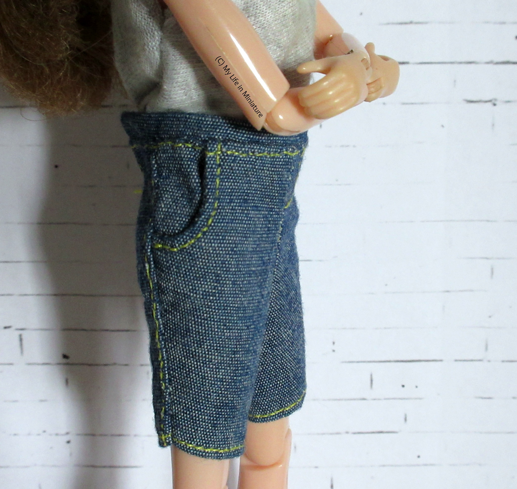 Side-on shot of the denim shorts, highlighting the pocket. The edge is curved in the style of denim jeans' pockets.