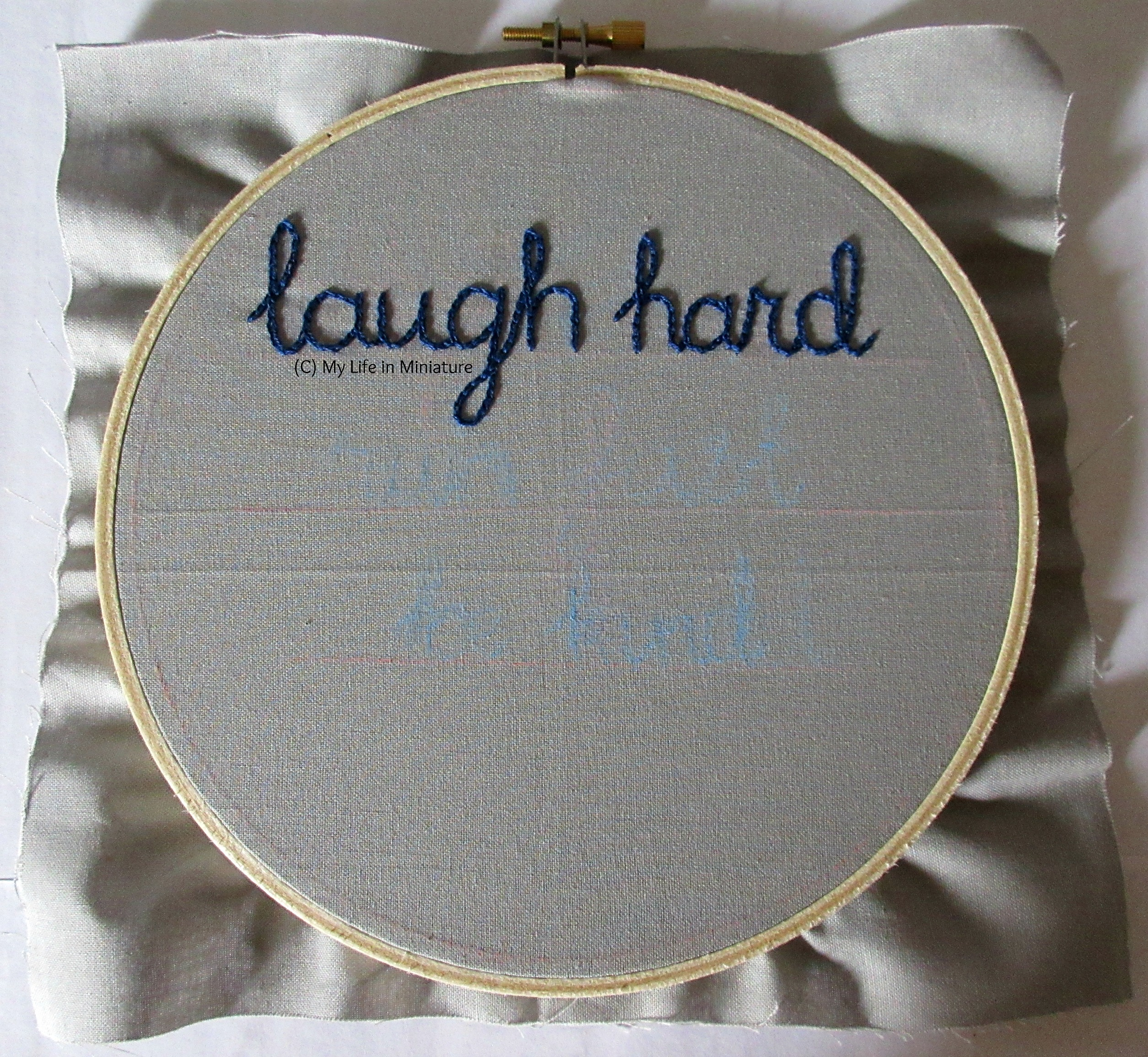 An embroidery hoop fills the image, strung with grey fabric. The phrase 'laugh hard' is stitched across the top third in dark blue chain stitch.