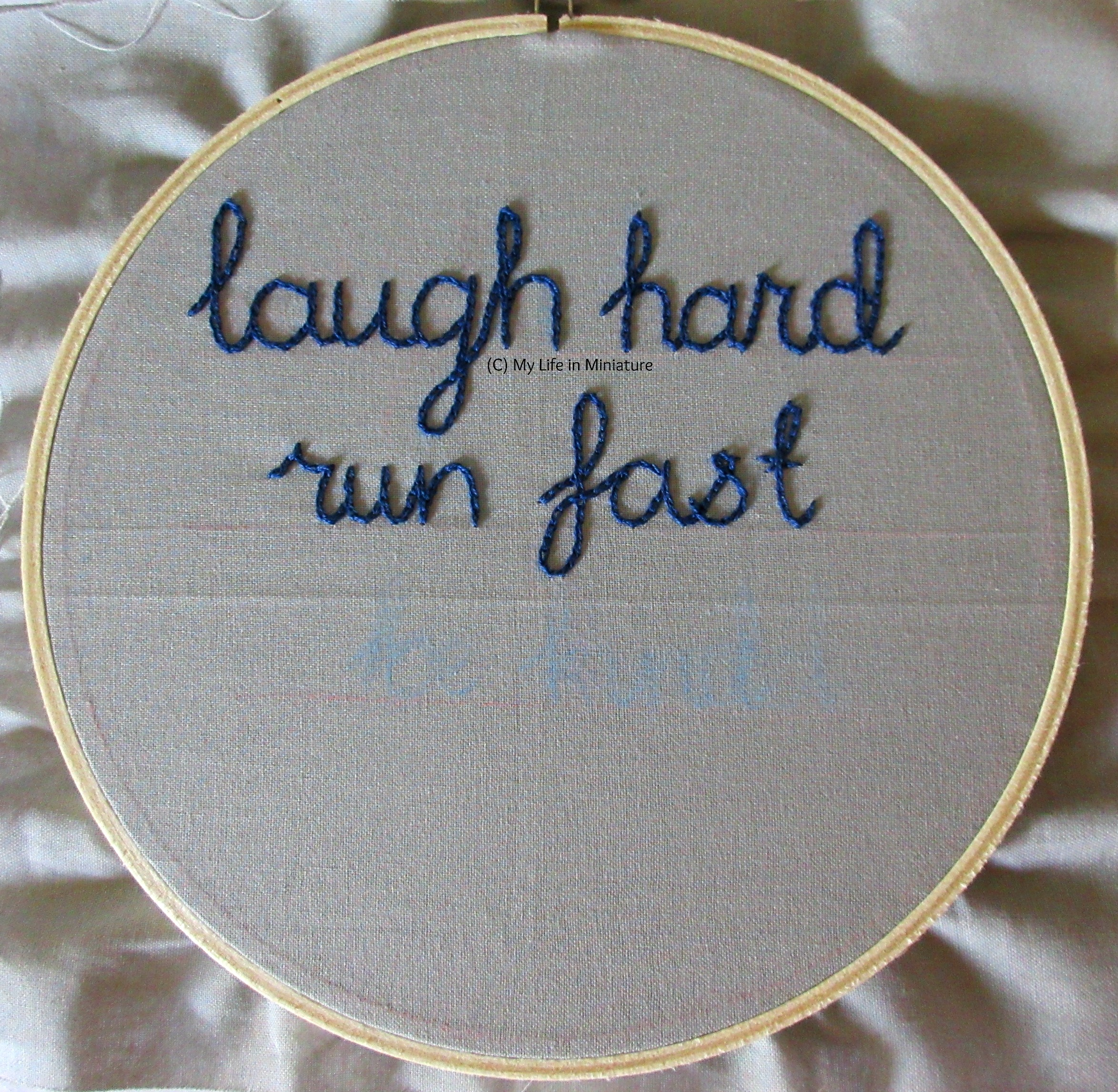 An embroidery hoop fills the image, strung with grey fabric. The phrase 'laugh hard; run fast' is stitched across the top half in dark blue chain stitch.