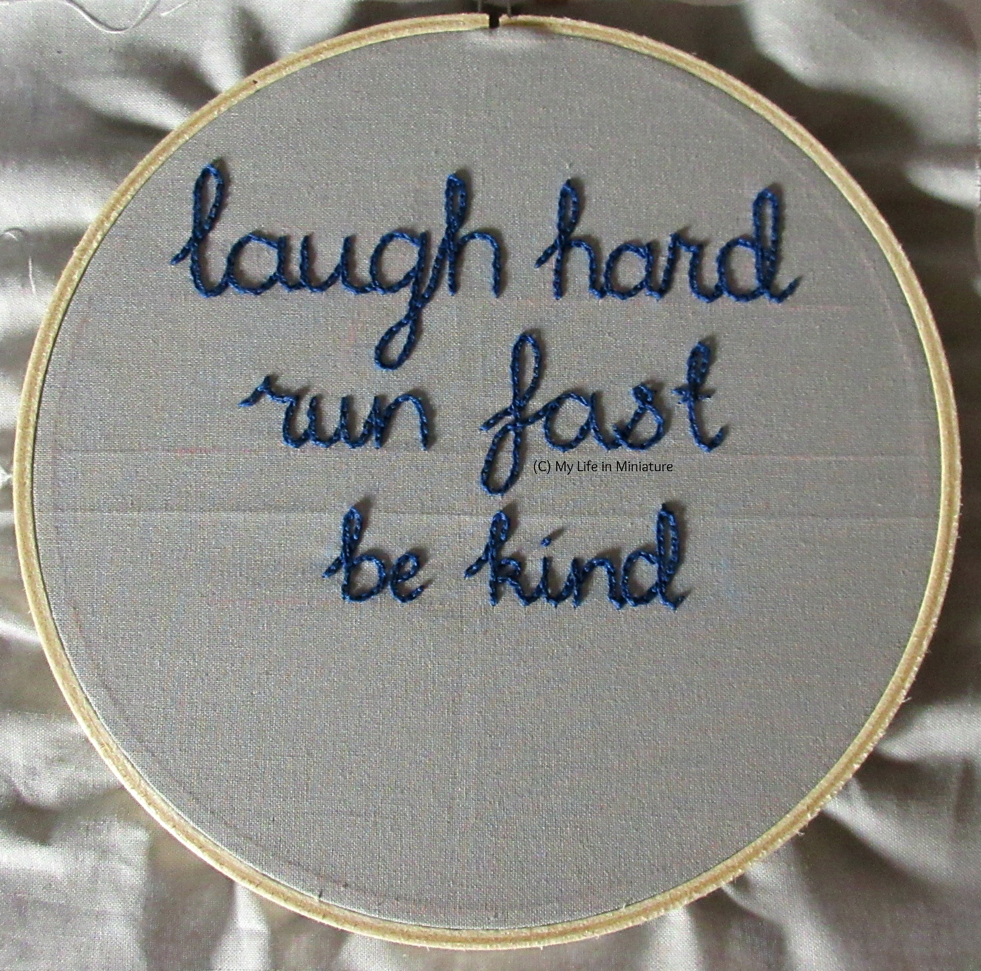 An embroidery hoop fills the image, strung with grey fabric. The phrase 'laugh hard; run fast; be kind' is stitched across the top two-thirds in dark blue chain stitch.