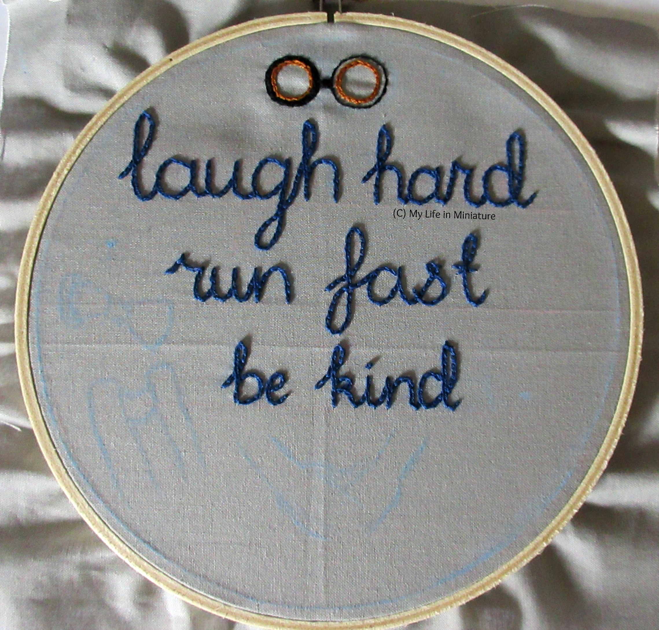 An embroidery hoop fills the image, strung with grey fabric. The phrase 'laugh hard; run fast; be kind' is stitched across the top two-thirds in dark blue chain stitch. Above 'laugh hard' is the beginnings of the eyepieces of some steampunk black and gold goggles.