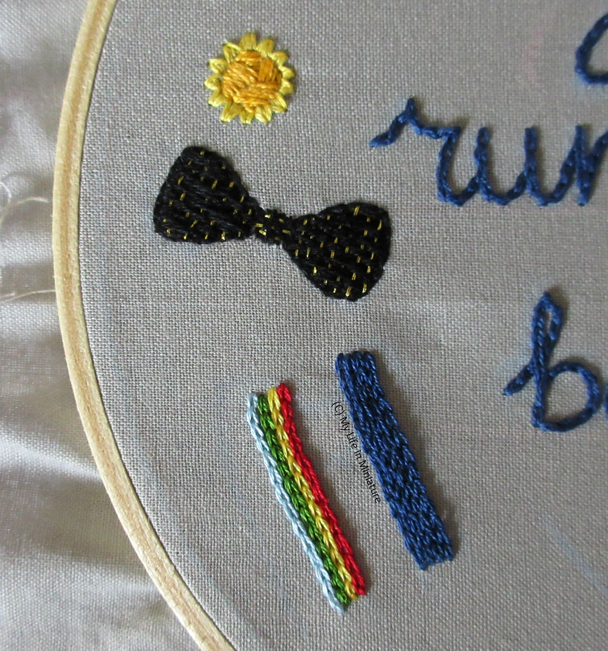 CLose-up of the motif below the daffodil on the hoop. It's a bow tie, stitched in black satin stitch that has been woven through with metallic gold thread.