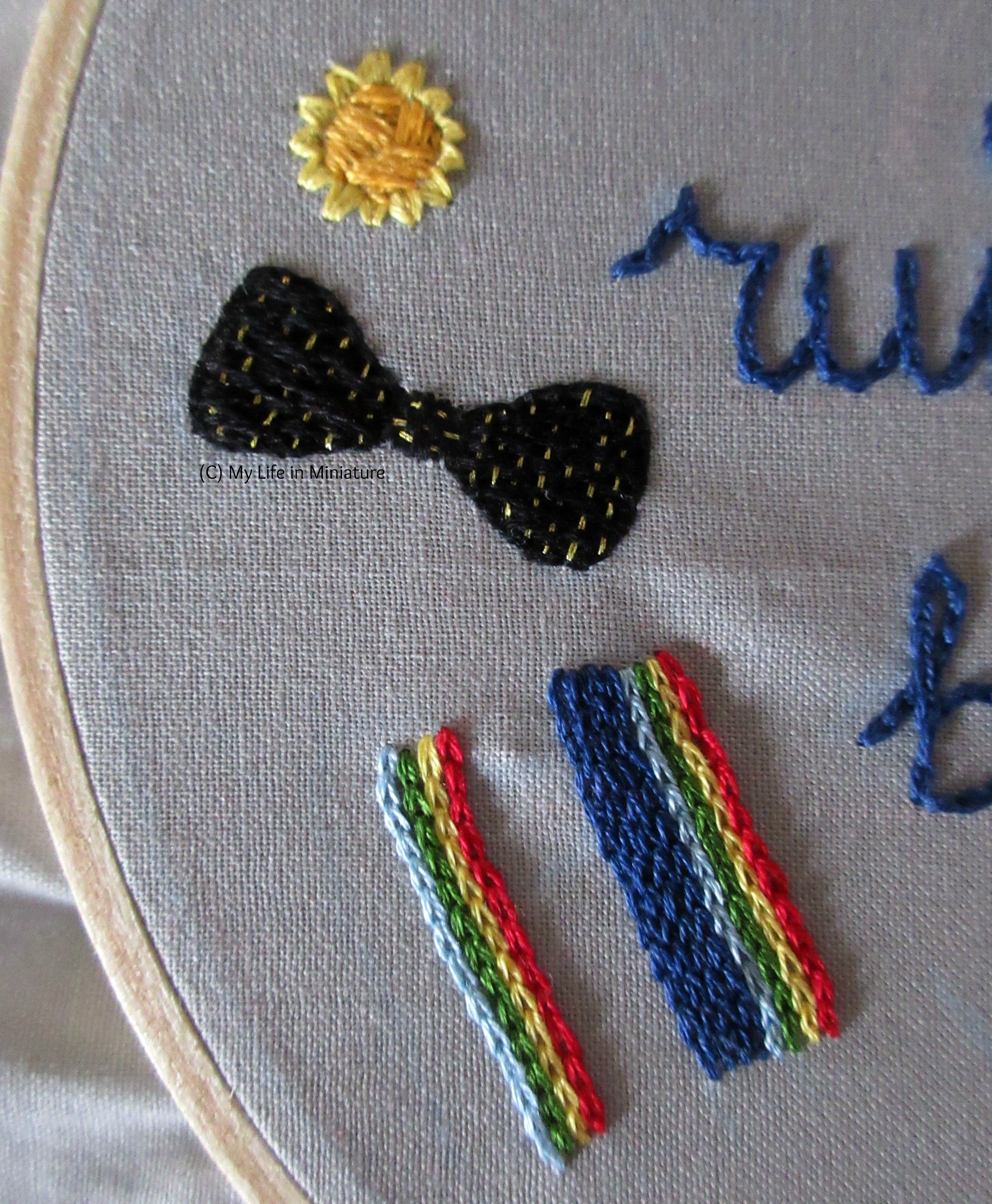 A shot of the daffodil motif, the bow tie, and the beginnings of a rainbow-striped scarf motif in a vertical row down one side of the Thirteenth Doctor embroidery hoop.