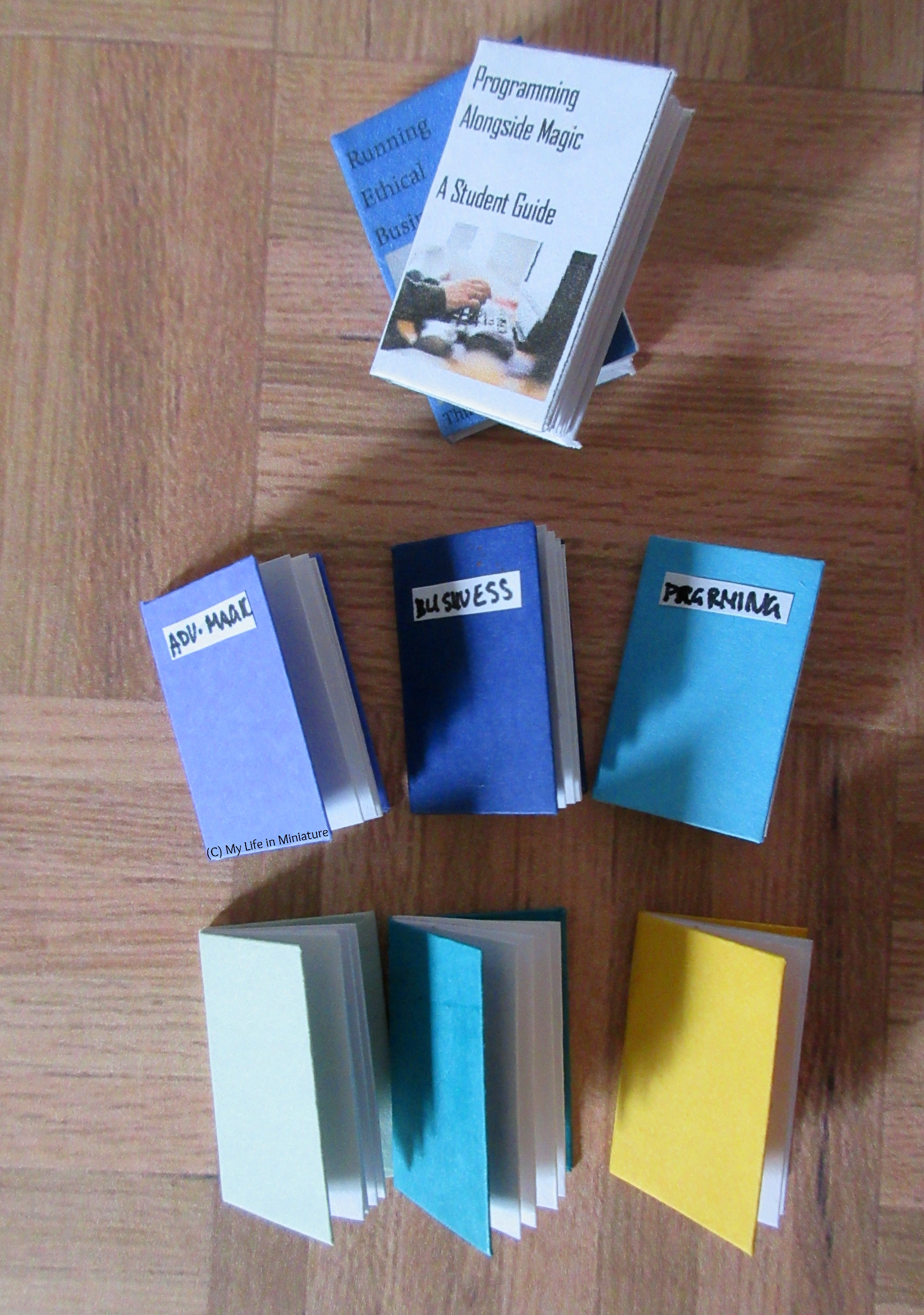 Six notebooks sit on a wood parquet background. They are various shades of blue, purple, green, and yellow. Three are labelled with different subjects. Two textbooks are above the notebooks for scale.