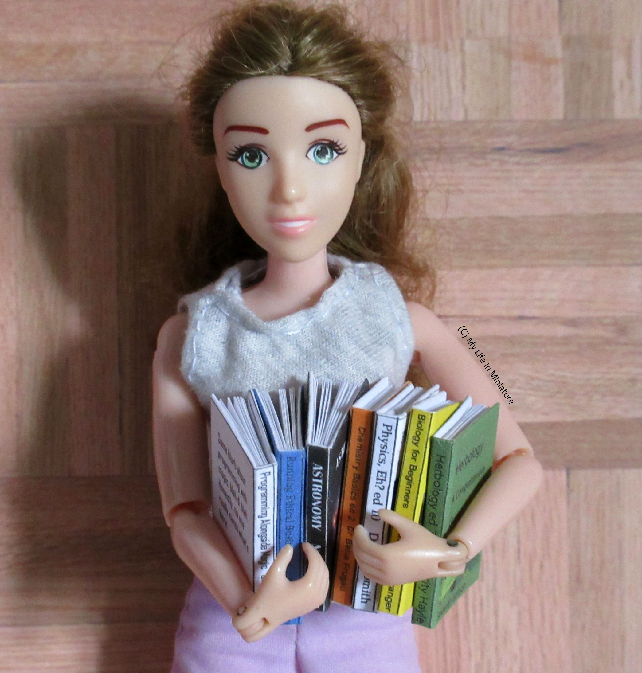 Sarah holds all seven textbooks in her arms, standing against a wood parquet background. She looks at the camera.