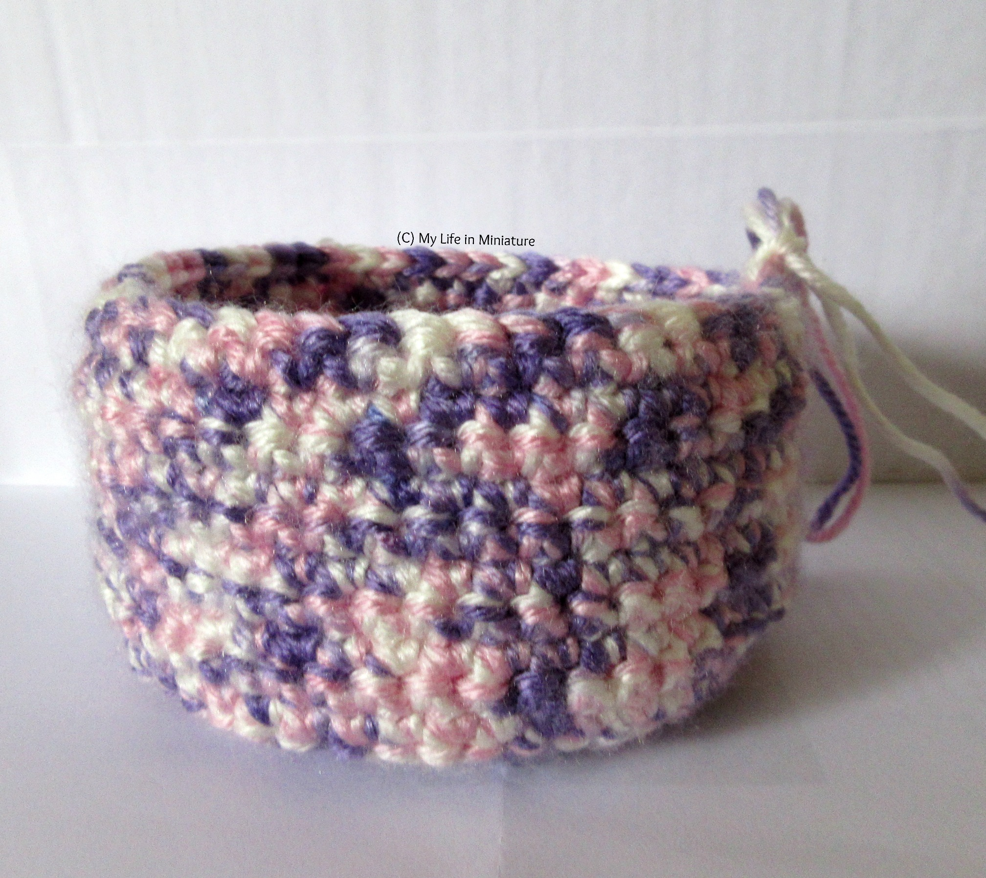 The pink, purple, and white crocheted nest has quite tall sides now, about 10 rounds. It's against a white background.