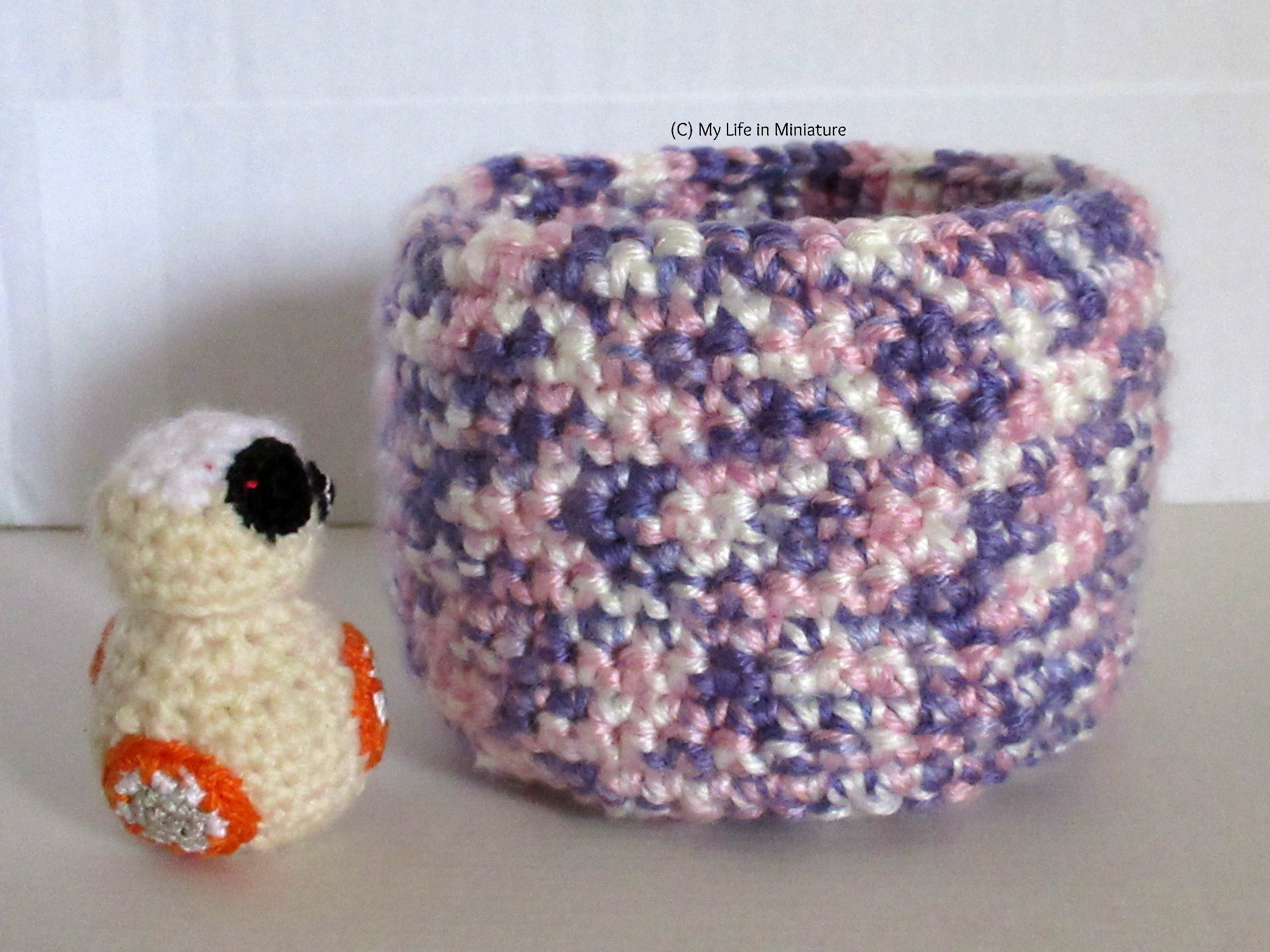 The finished crocheted nest stands next to BB-8 for scale against a white background. The nest is about 1 and a half times the height of BB-8.