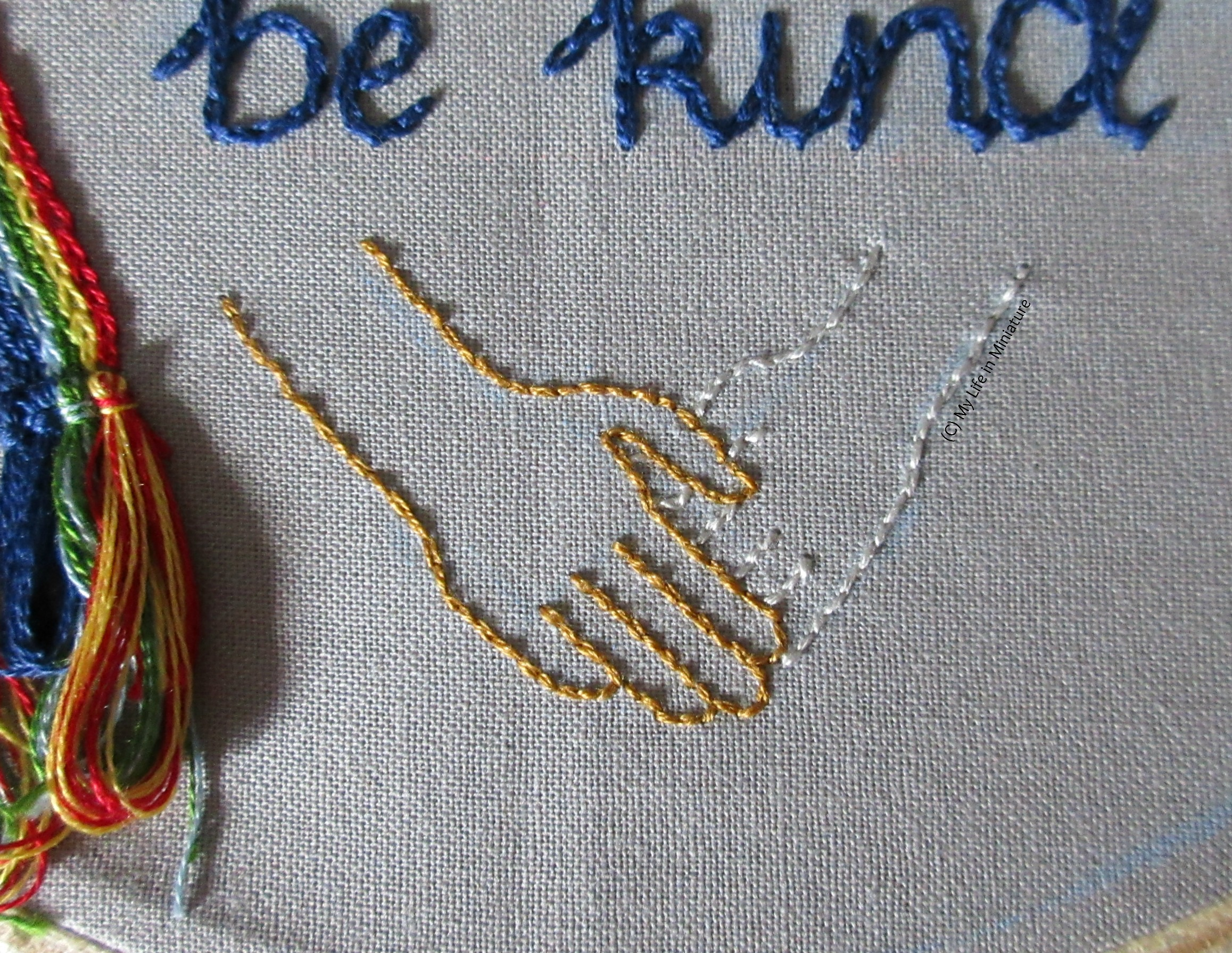 Image shows the bottom of the grey hoop. The gold hand from the image before is visible, now interlocking with another hand, outlined in silver.