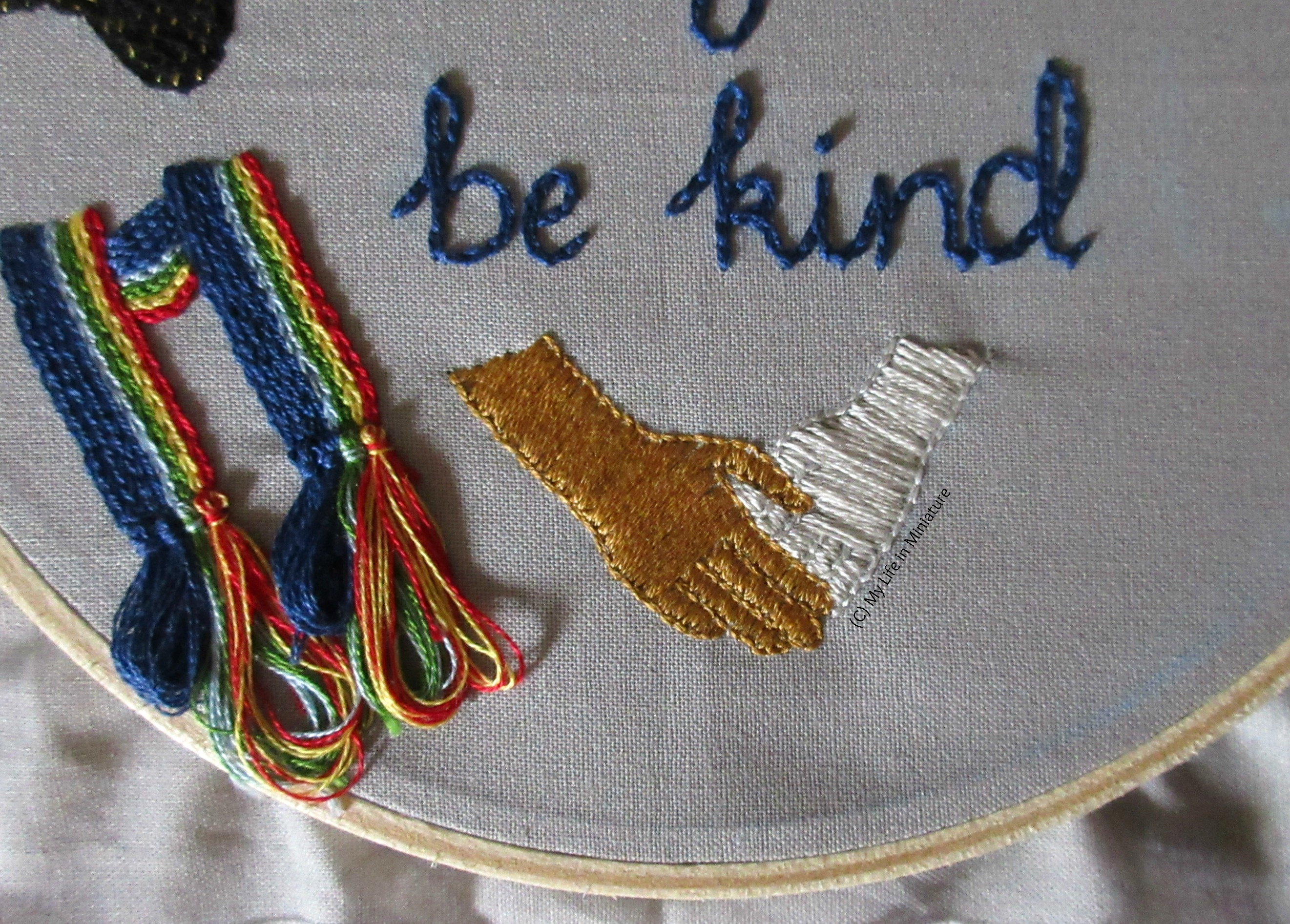 Shot from further back of the bottom of the grey hoop. The scarf tassels are visible on the left, and the two hands are now both filled in. The phrase 'be kind' is visible in dark blue above the hands.