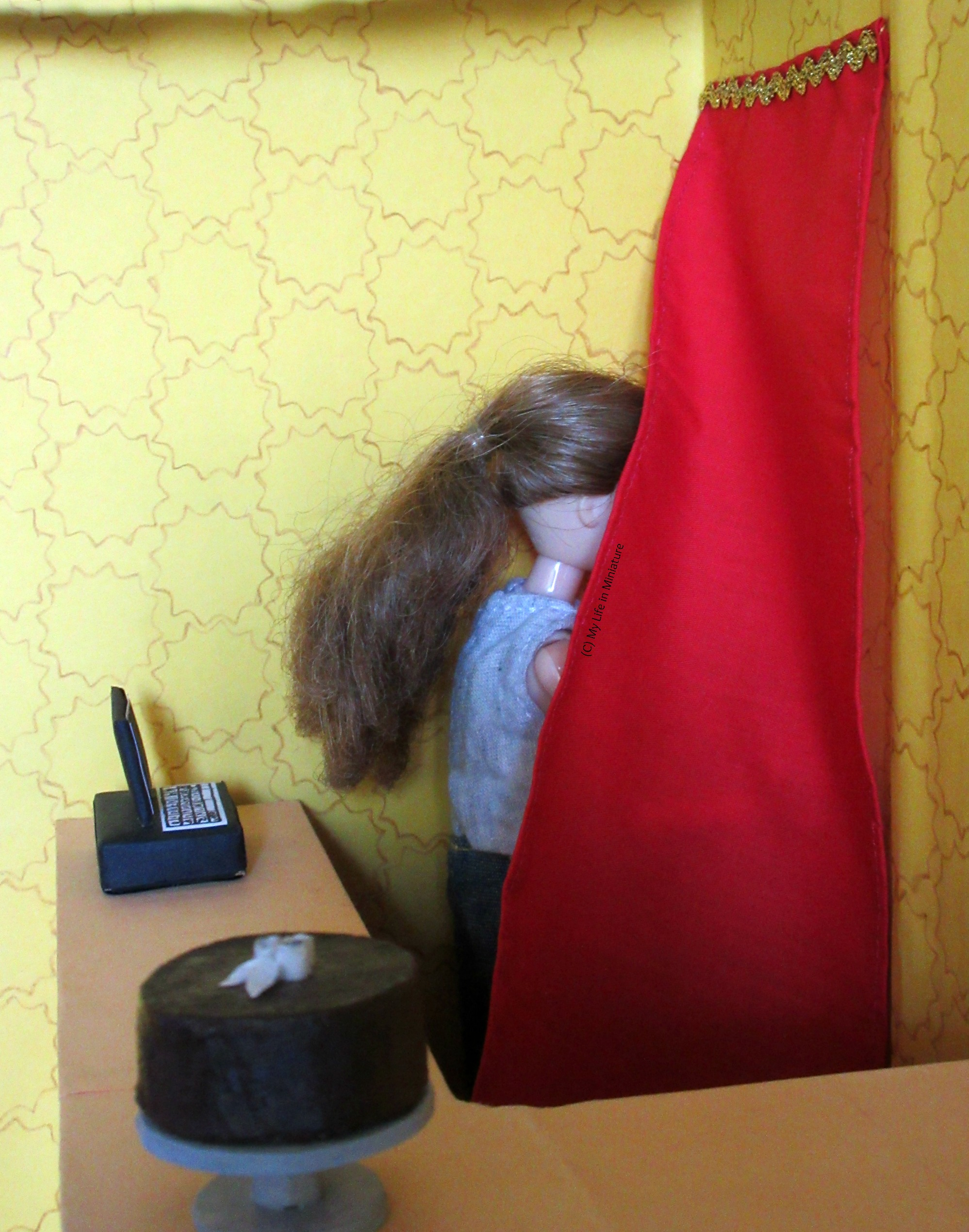 Sarah is holding the red curtain aside to go through it to the back rooms of Tea at Yaz's. The curved counter's top is visible in the foreground.