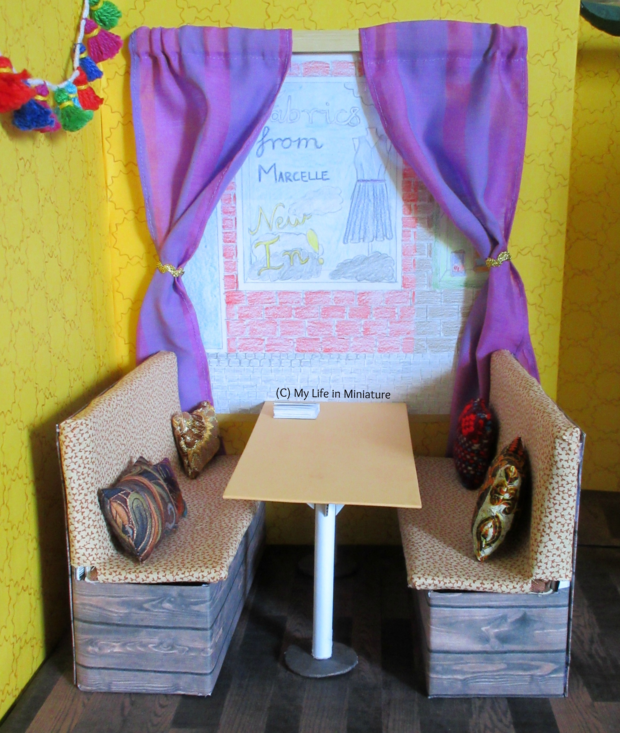 The booth area of Tea at Yaz's is visible. There are two purple curtains over the front window, pulled aside with metallic gold bric-a-brac. The curtains are on a wooden rail.