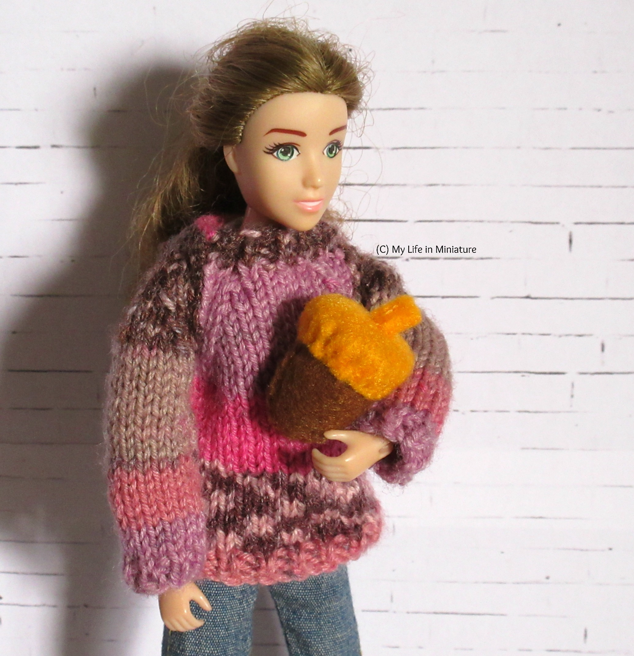 Sarah holds one of the smaller acorns in her arm. It's far too large to be a realistic size. She's in a pink jumper, and is looking at the acorn.